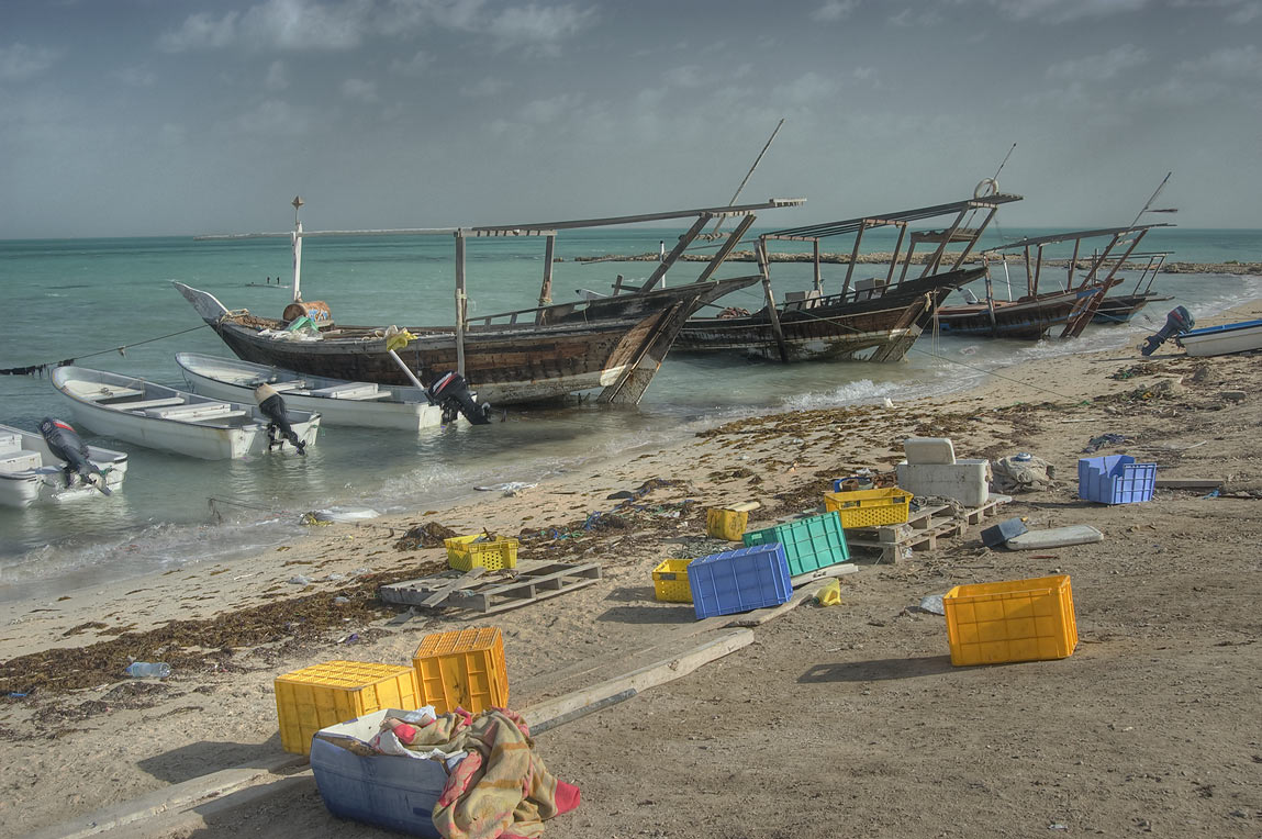 Closed fresh fish sale and dhow boats on a beach in Ruwais on north coast. Qatar