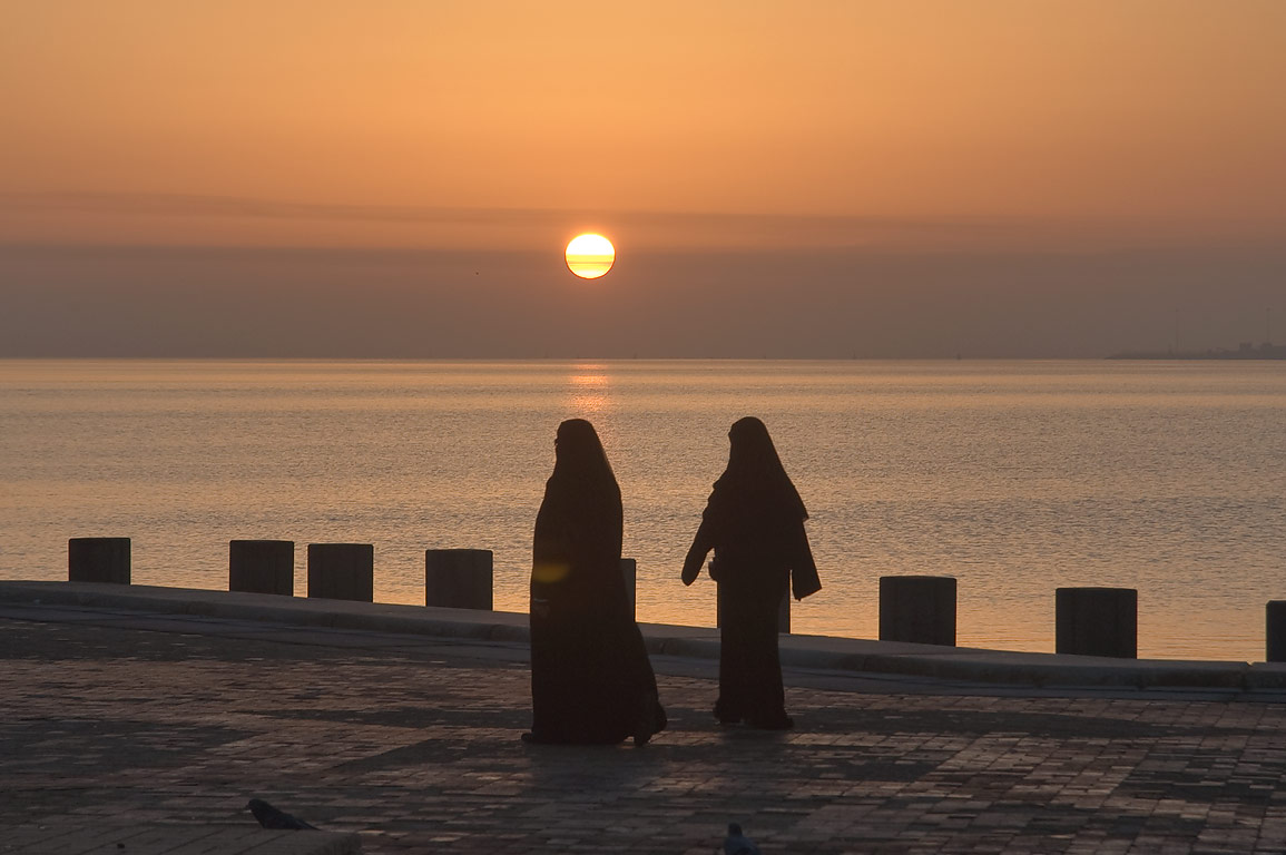 Jogging women in black gown on Corniche (waterfront promenade) at sunrise. Doha, Qatar