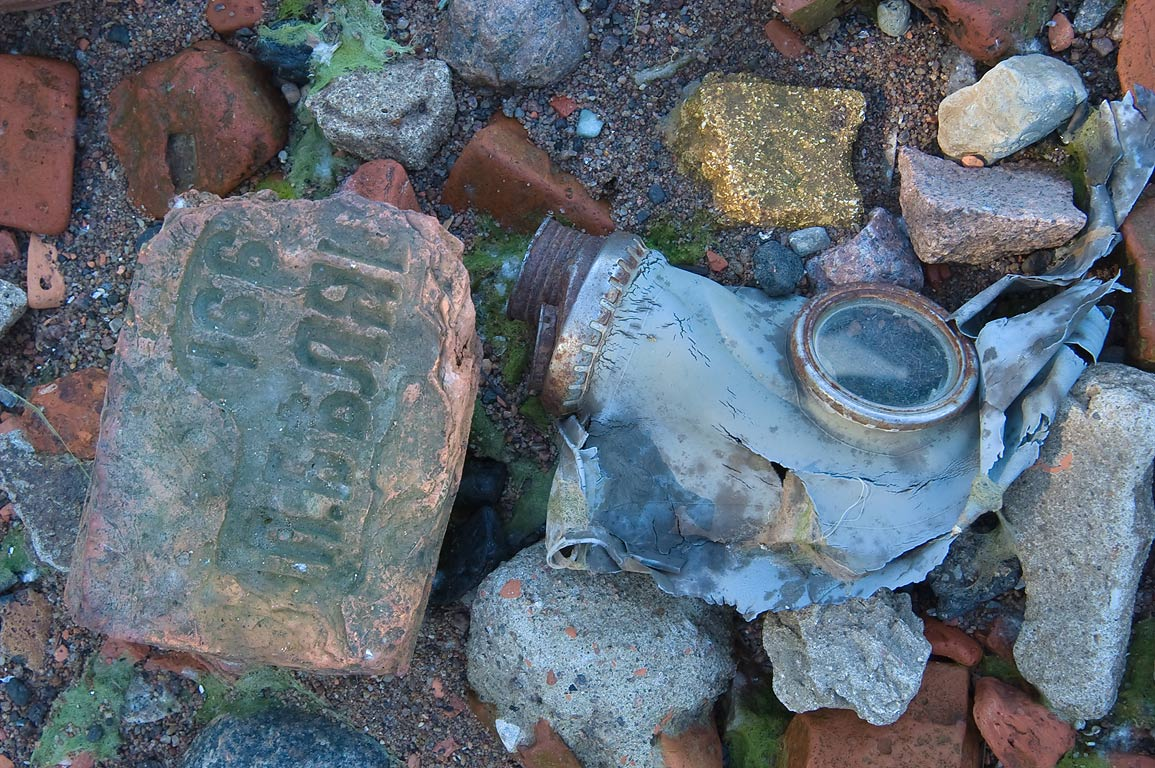 Old bricks and a gas mask on northern city beach...a suburb of St.Petersburg, Russia