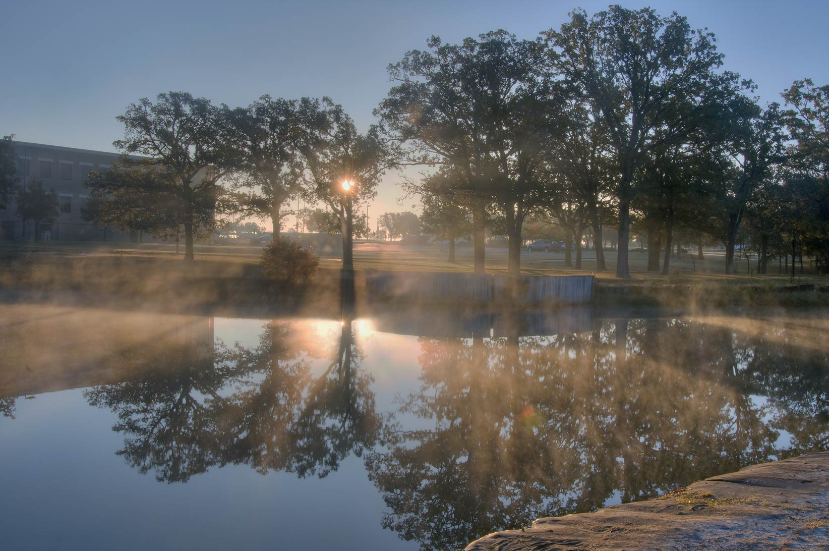 Misty sunrise over a pond of Research Park in fog...M University. College Station, Texas