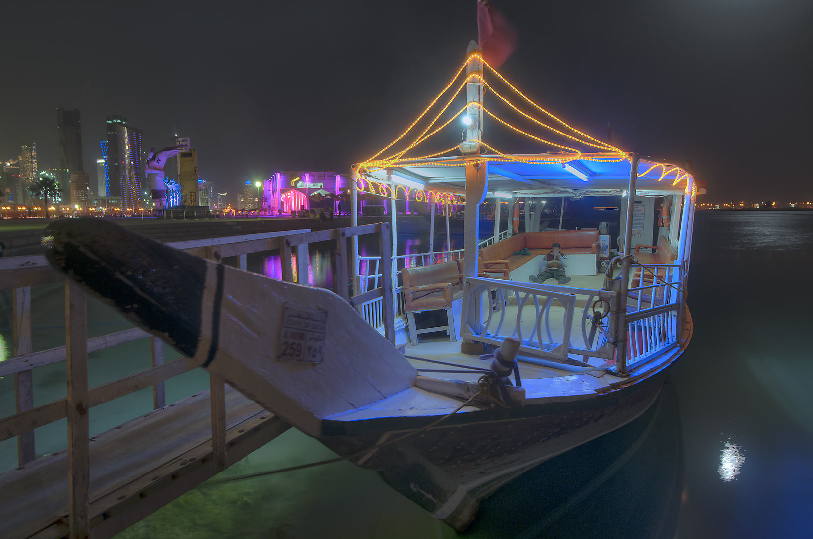 Dhow boat with lights on Corniche at evening. Doha, Qatar