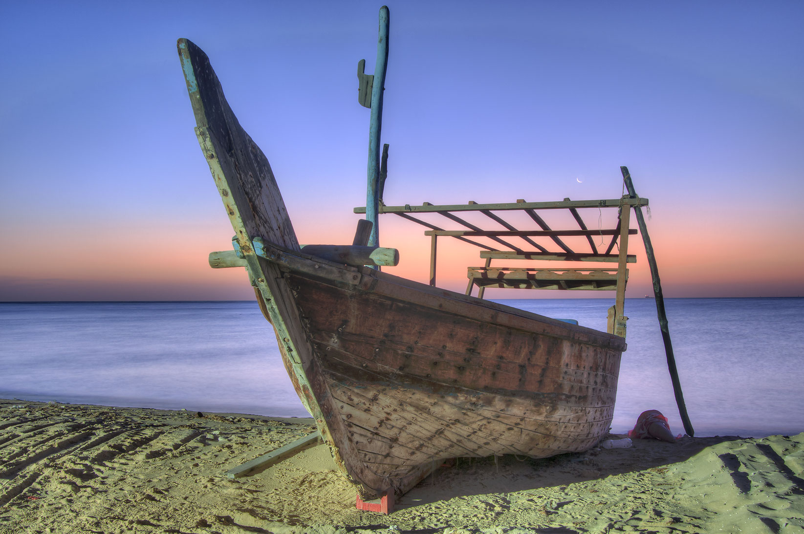 Dhow fishing boat on a beach at sunrise. Al Wakrah, Qatar