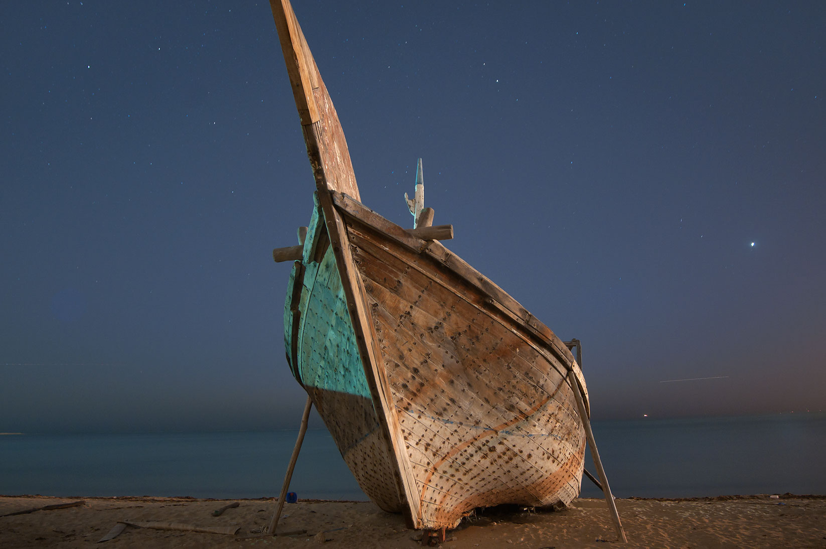 Dhow fishing boat on a beach in heritage village at early morning. Al Wakrah, Qatar