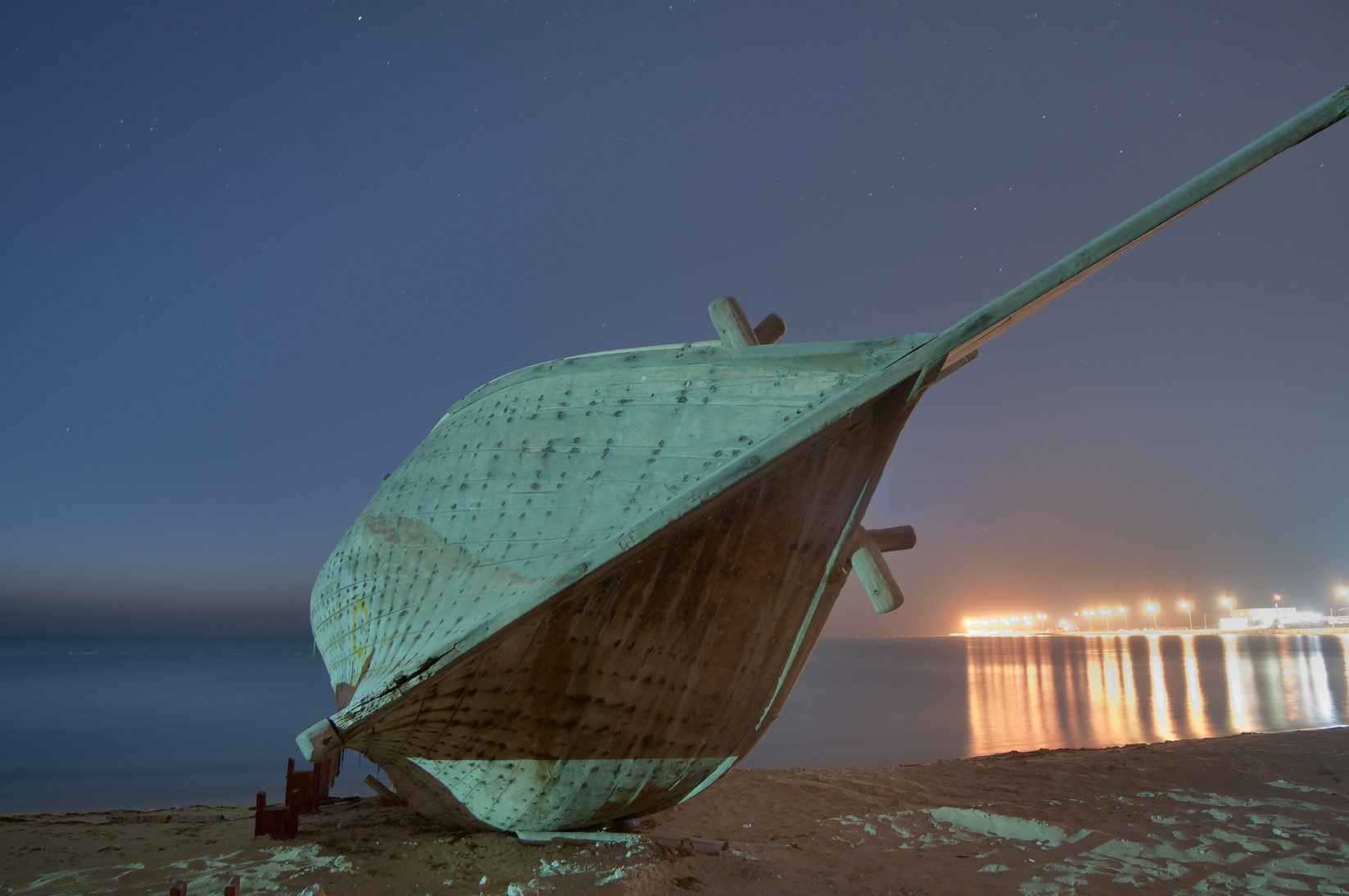 Hull of a fishing boat on a beach near heritage village at morning dusk. Al Wakrah, Qatar