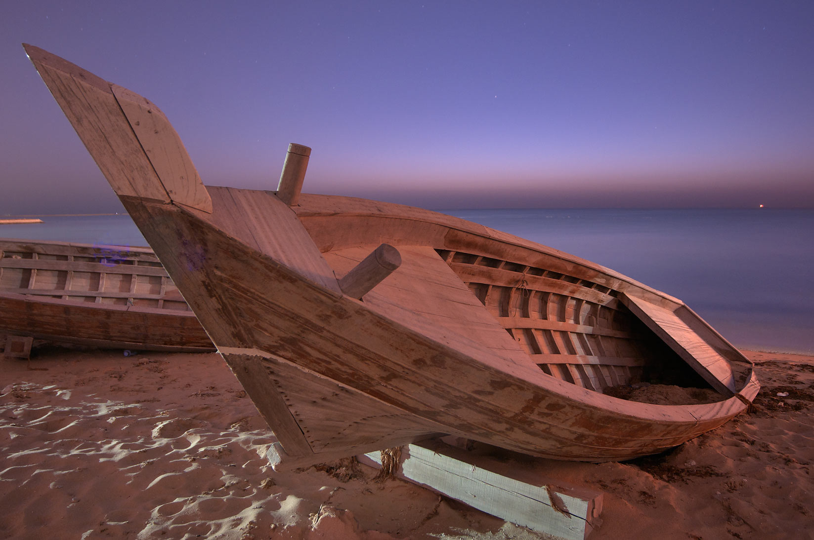 Fishing boats on a beach near heritage village at sunrise. Al Wakrah, Qatar