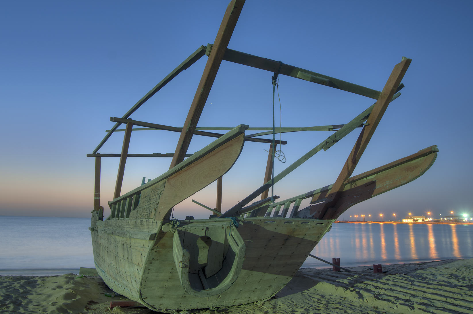 Beached dhow boat near heritage village at morning. Al Wakrah, Qatar