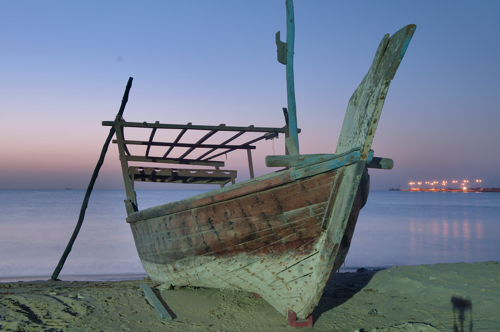 Beached dhow boat near heritage village at morning dusk. Al Wakrah, Qatar