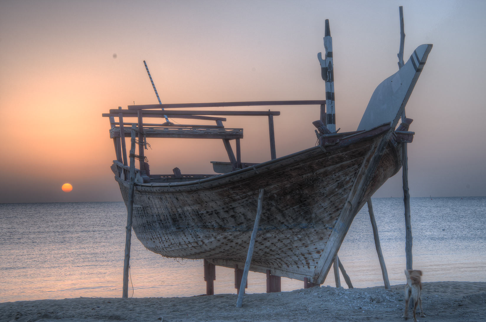 Silhouette of a fishing boat on a beach at sunrise. Al Wakrah, Qatar