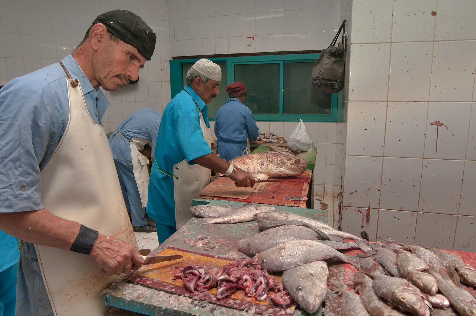 Workers cleaning fish in Central Fish Market. Doha, Qatar