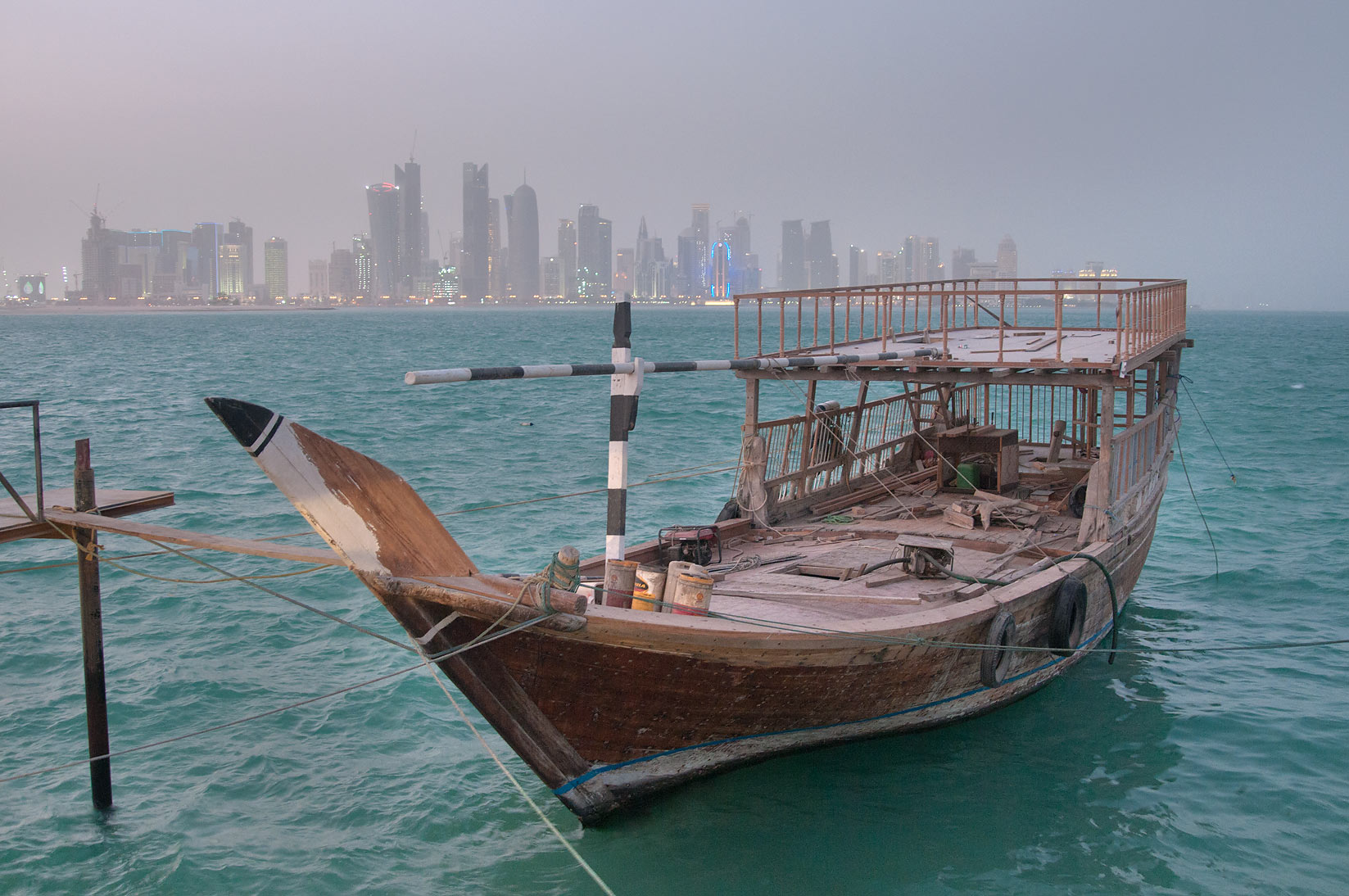 Dhow boat in fishing harbor, with West Bay in background. Doha, Qatar