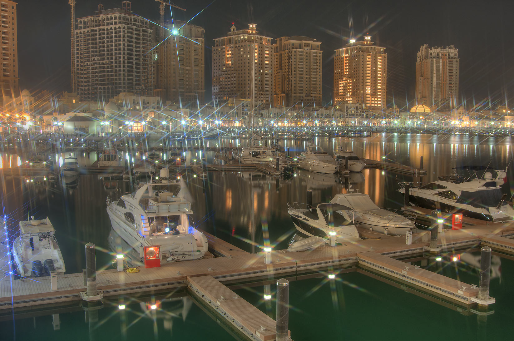 Boats docked in marina of Porto Arabia in Pearl Qatar development at evening. Doha, Qatar