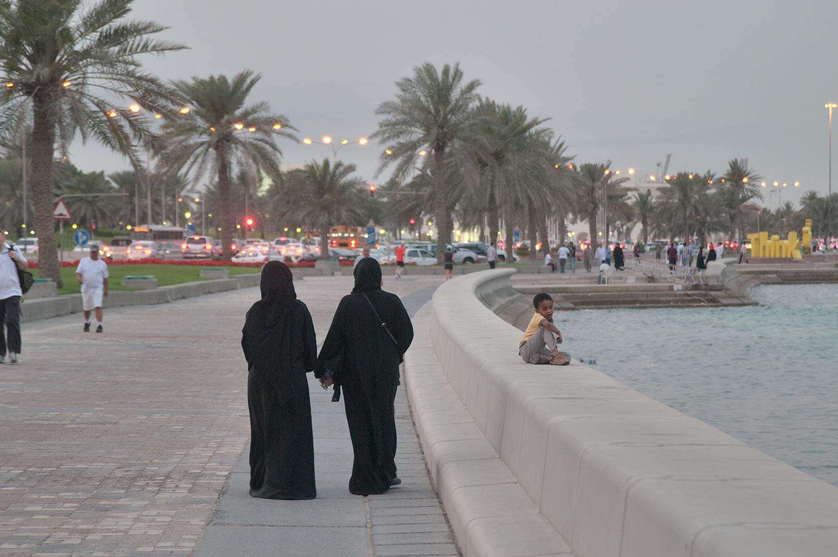 Women in abaya walking on Corniche (seafront promenade) at evening. Doha, Qatar