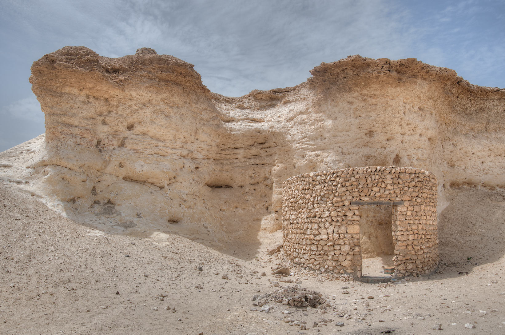 Stone hut nestling under a limestone hill...area, north from Zekreet. Qatar