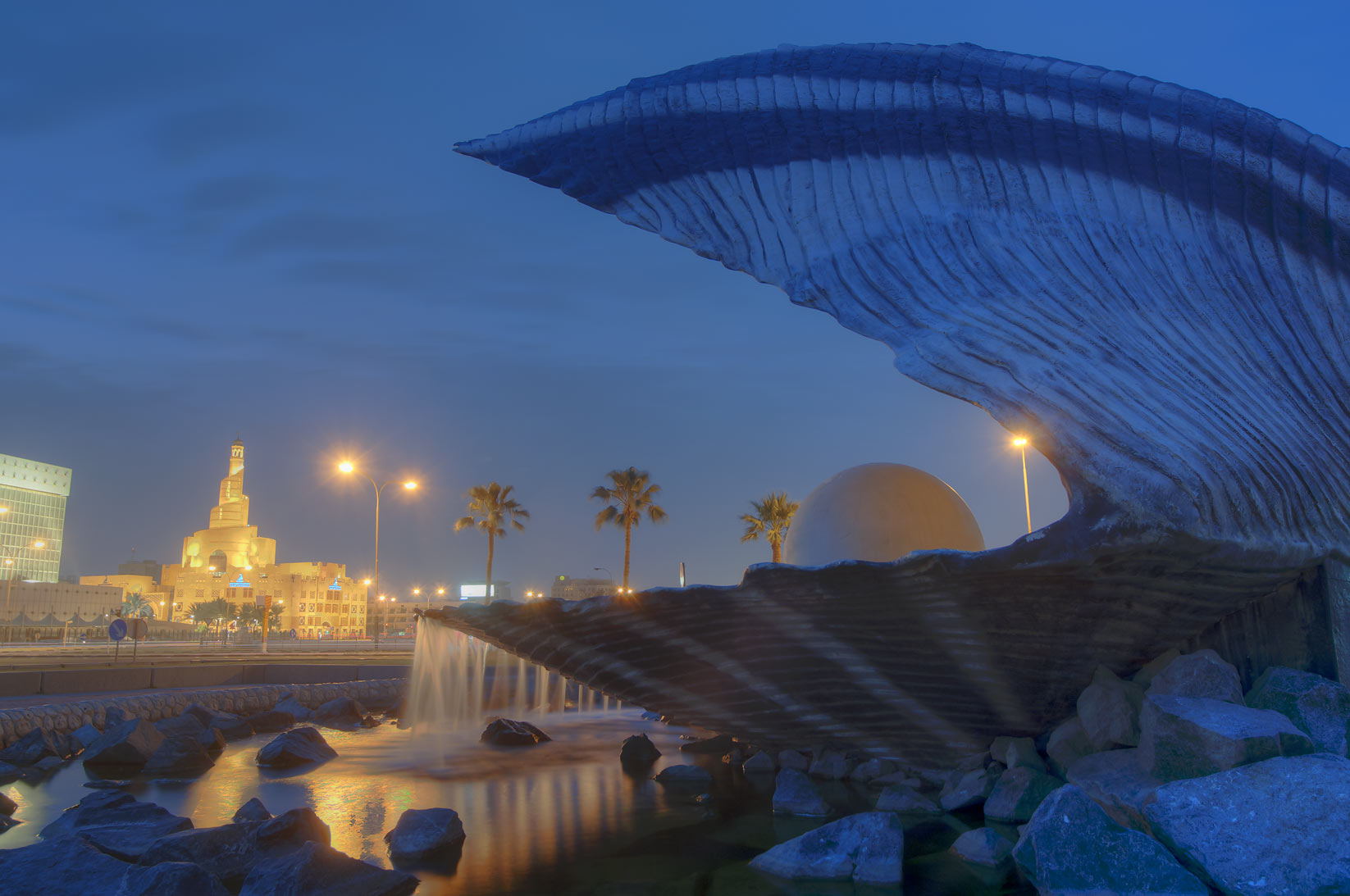 Oyster and Pearl Fountain on Corniche, with spiral mosque in background. Doha, Qatar