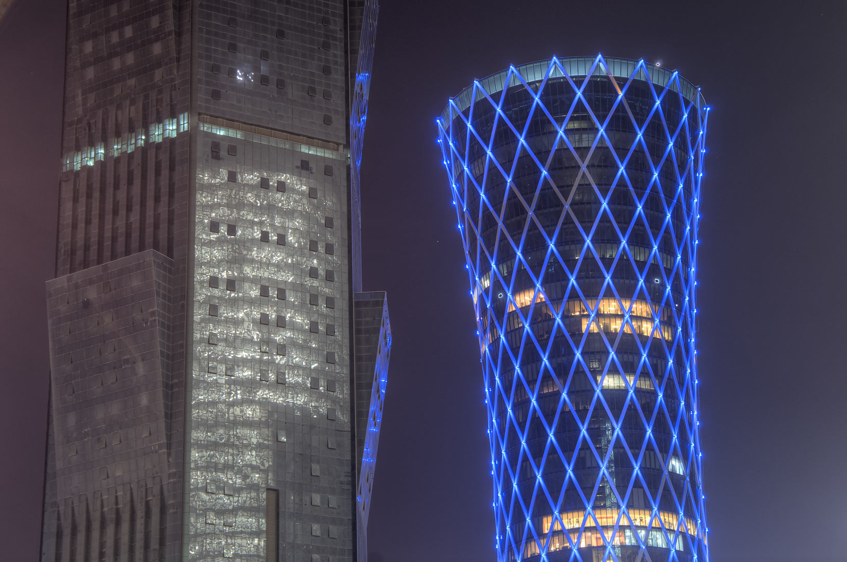Palm Tower with light reflections and Tornado Tower in West Bay at evening. Doha, Qatar