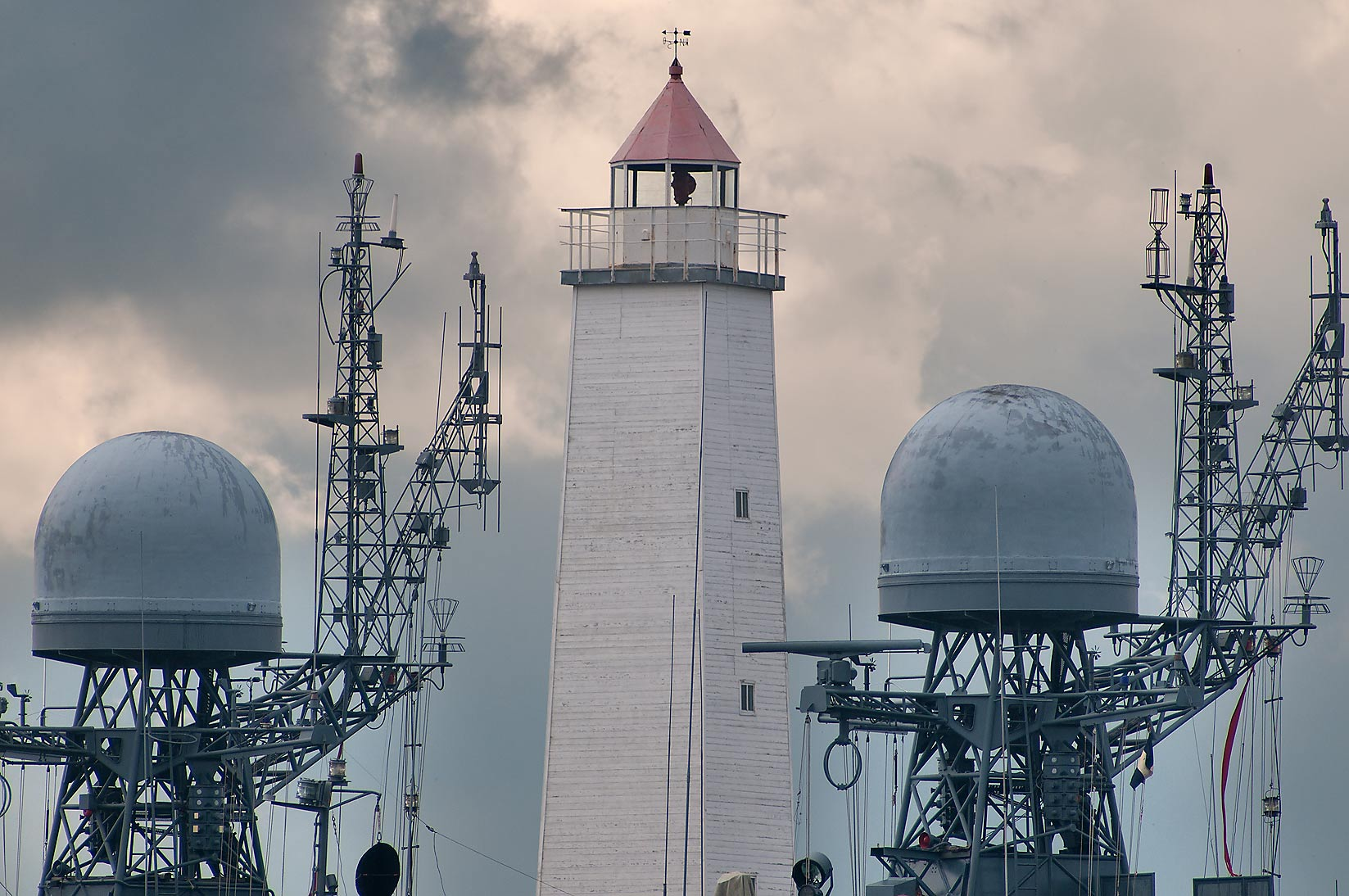 Lighthouse and military ships from Petrovsky Park in Kronstadt. St.Petersburg, Russia