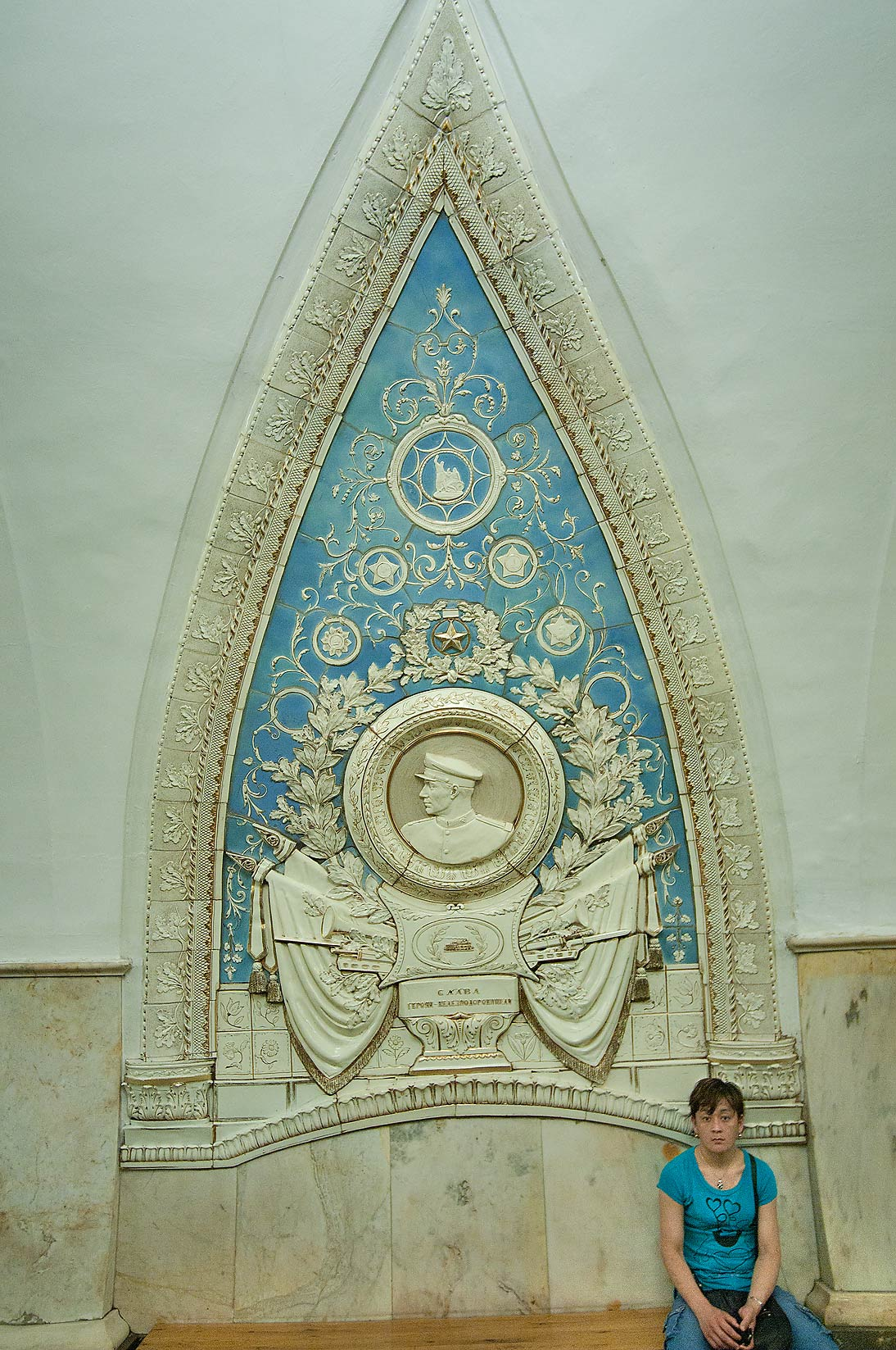 Passenger sitting under a patriotic decoration in...Metro (subway) station. Moscow, Russia