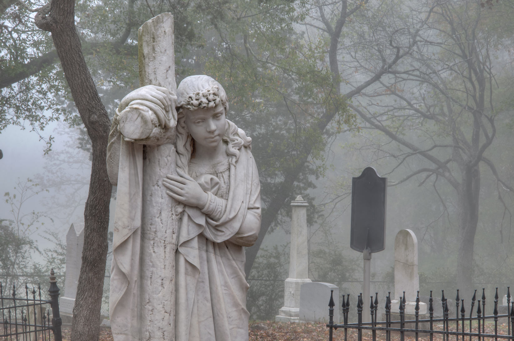 Marble sculpture of a woman hanging a cross in Oakwood Cemetery in fog. Huntsville, Texas