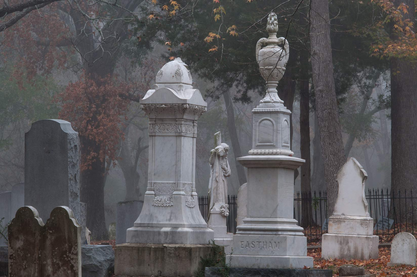 Decorated tombs of Oakwood Cemetery in fog. Huntsville, Texas