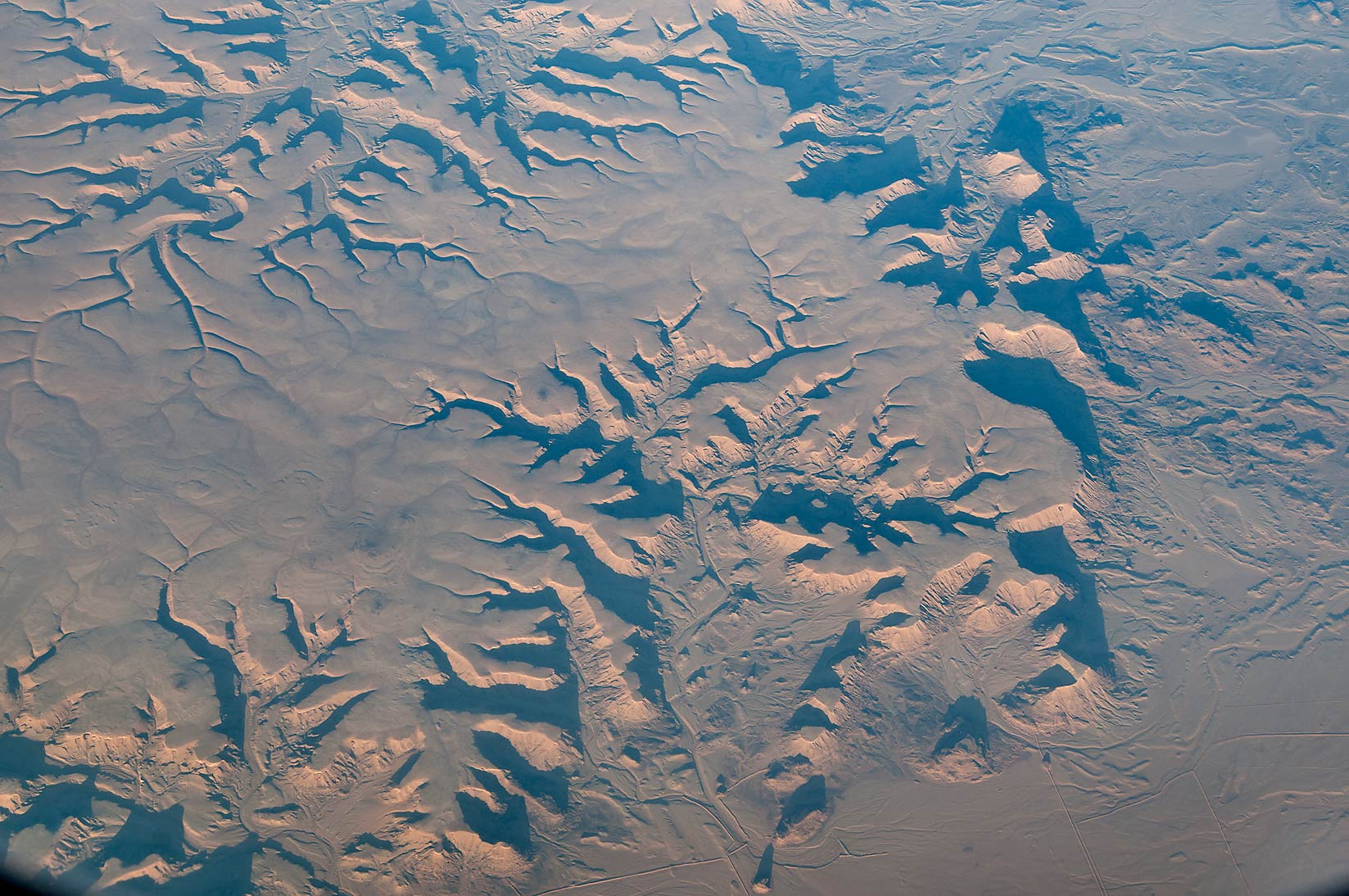 Al Jawf promontory, north-west from Khashm al...window of a plane from Houston to Doha