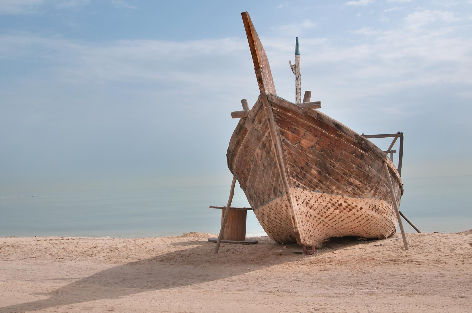 Beached dhow fishing wooden boat. Al Wakrah, Qatar