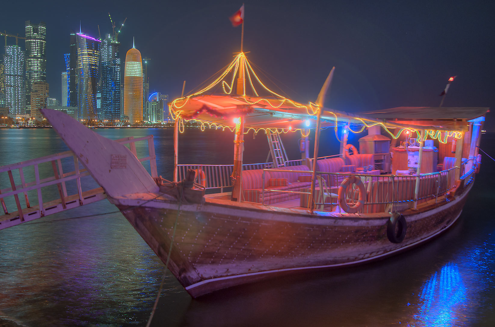 Illuminated dhow boat on Corniche near Balhambar...West Bay in background. Doha, Qatar