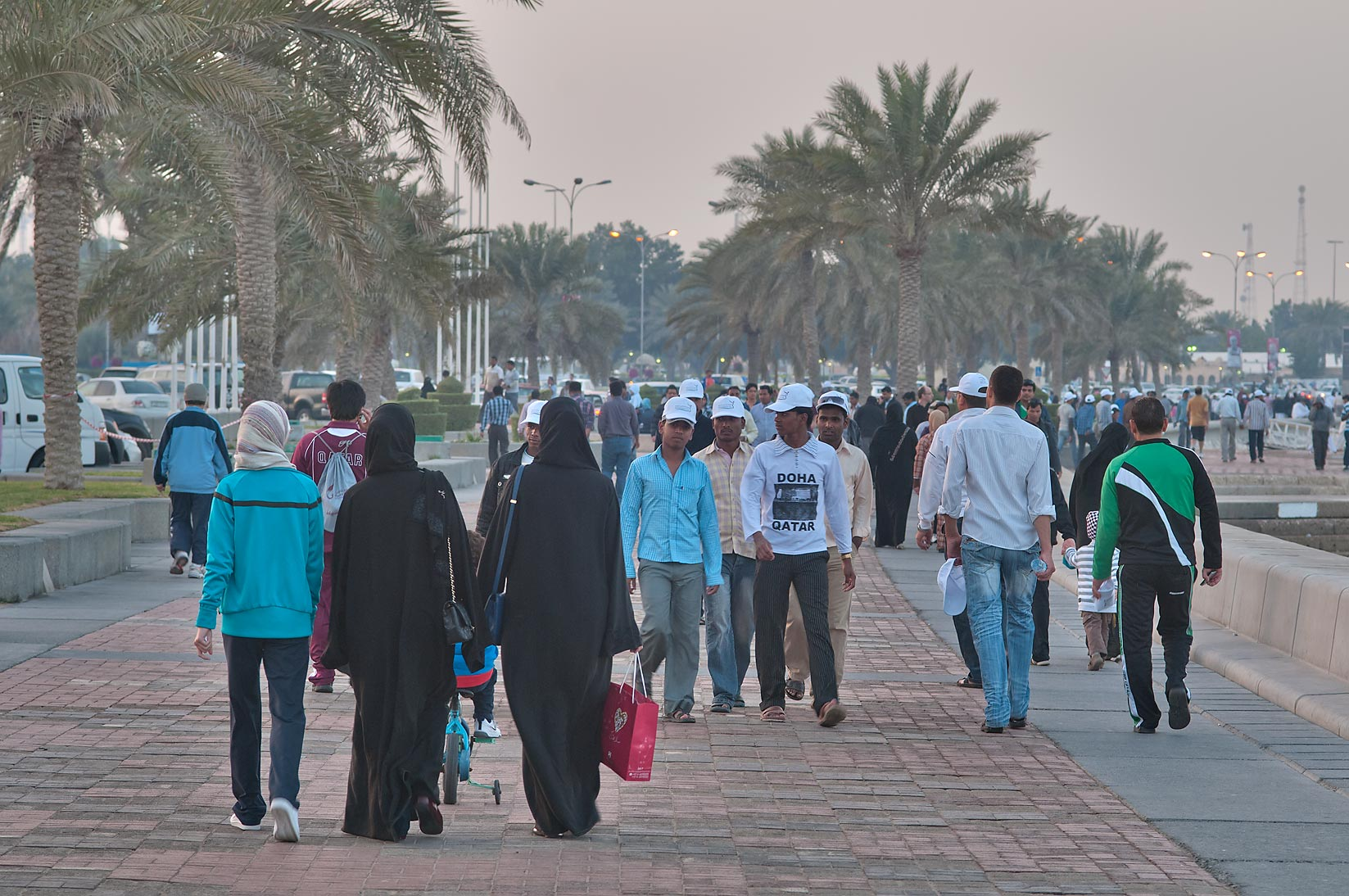 Crowds of people walking on Corniche during Sports Day holiday. Doha, Qatar