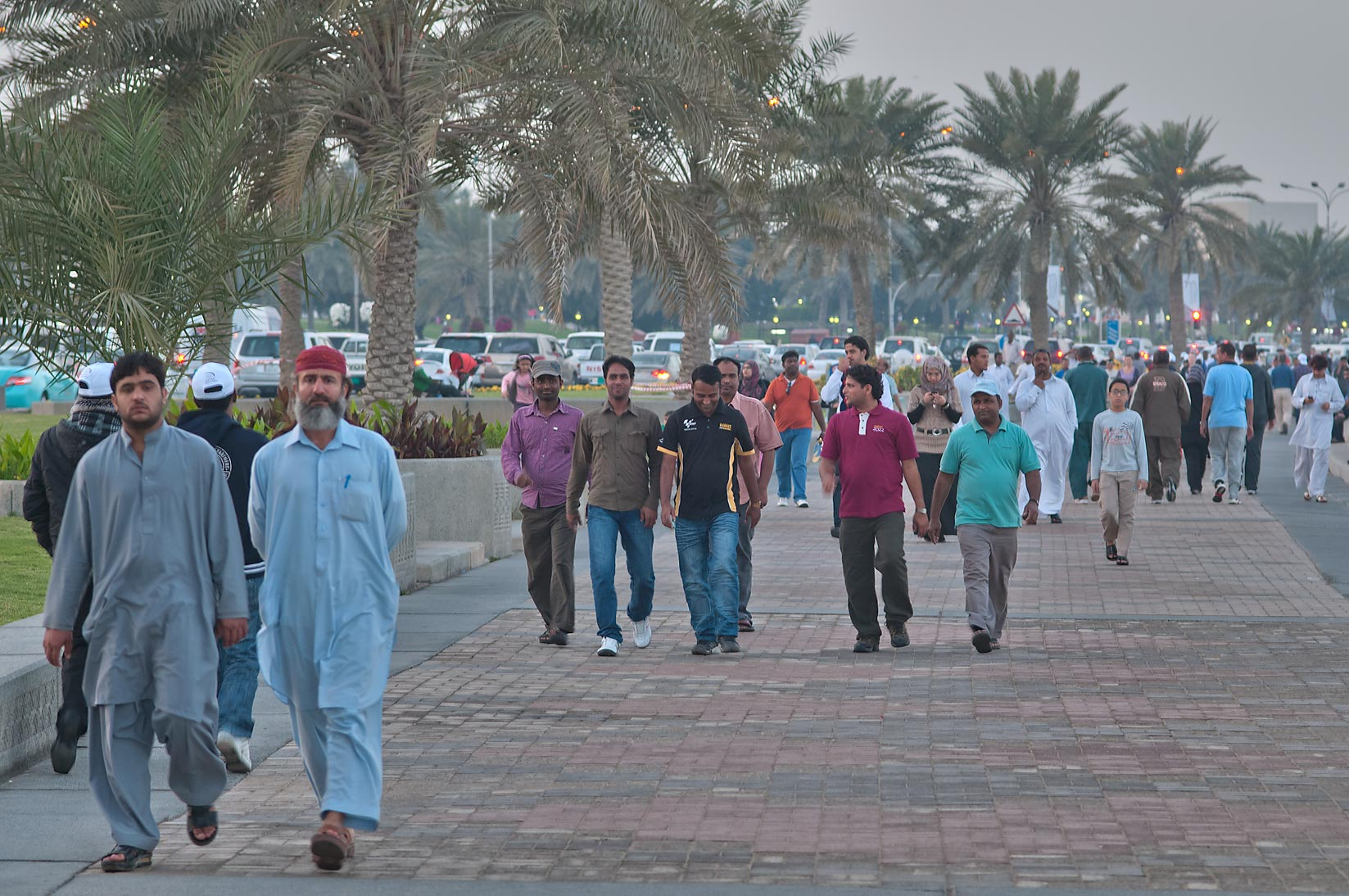 People walking on Corniche during Sports Day holiday. Doha, Qatar
