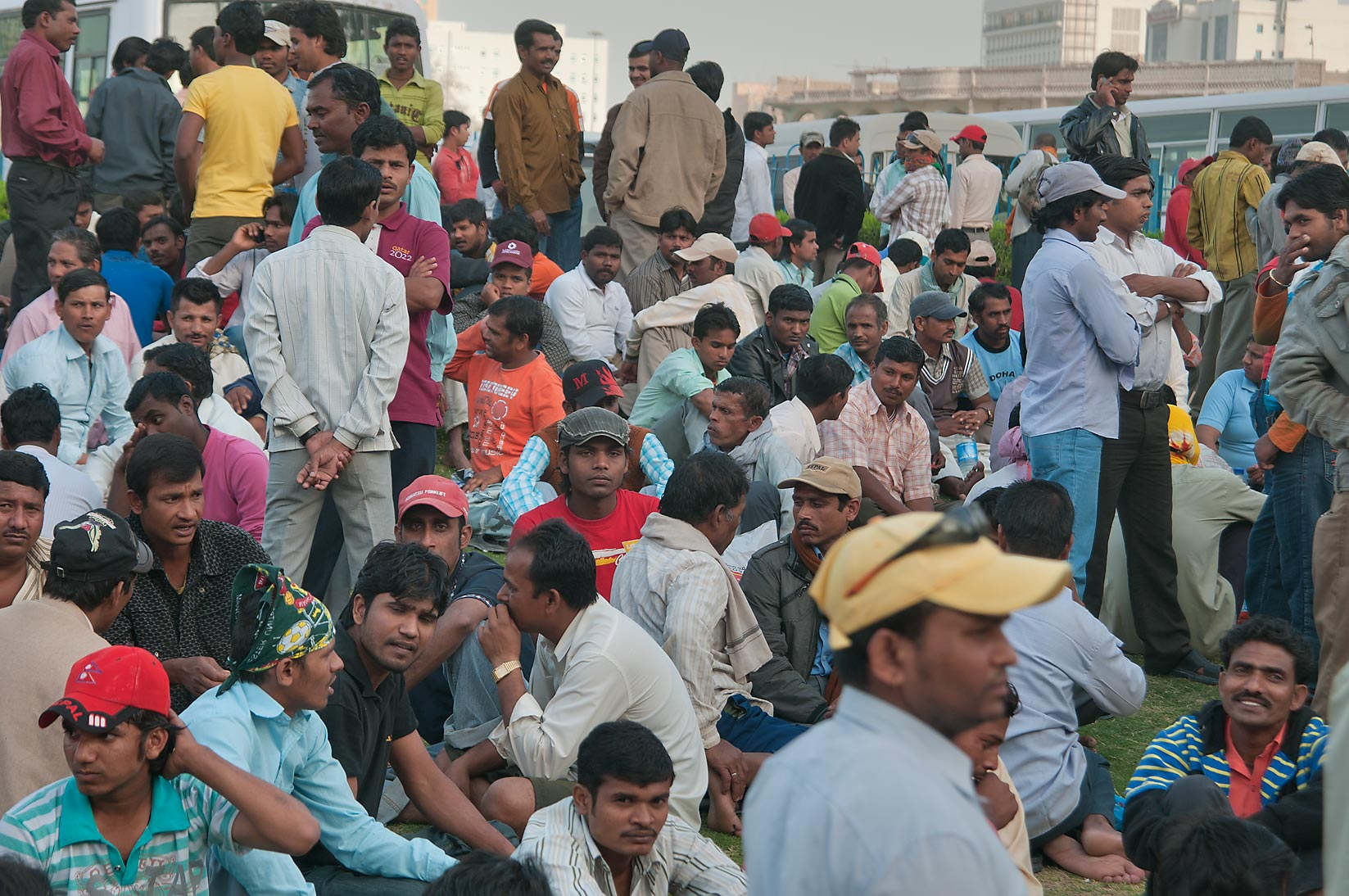 Workers socializing on Friday evening on a lawn...Al Ghanim) Bus Station. Doha, Qatar