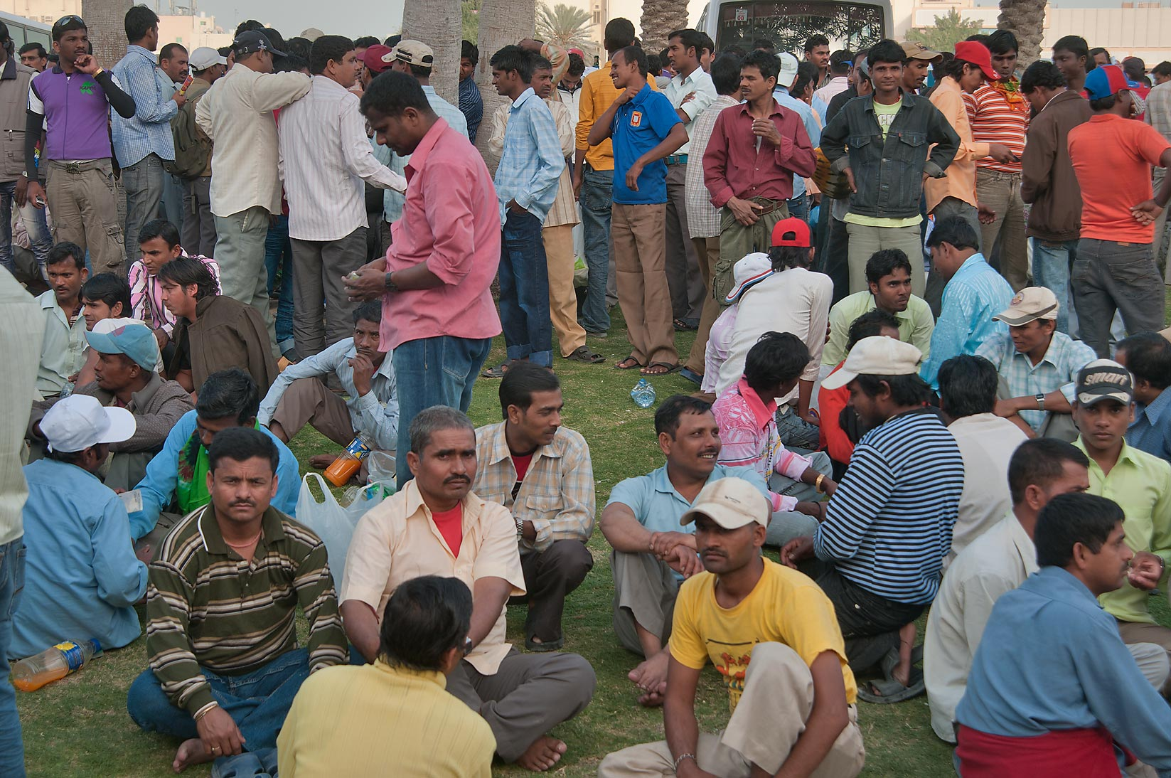 Workers gathering on Friday evening on a lawn...Al Ghanim) Bus Station. Doha, Qatar