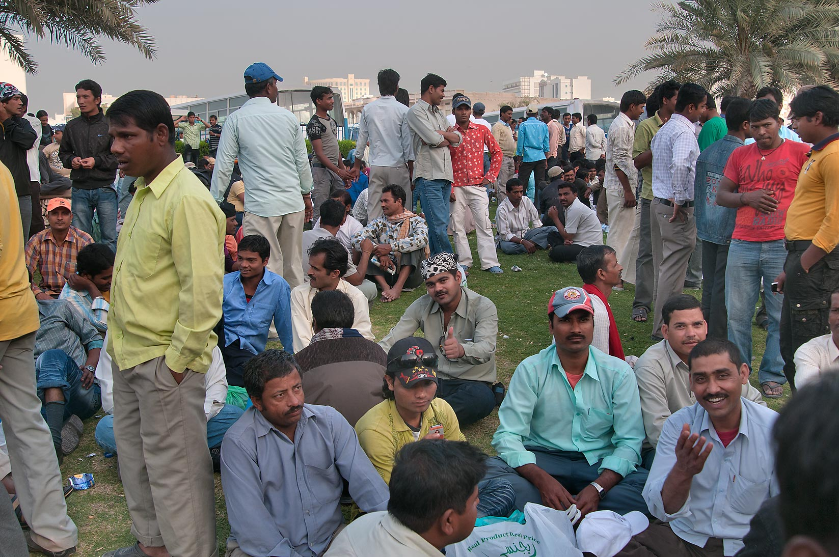 Migrant workers enjoy Friday weekend on a lawn...Al Ghanim) Bus Station. Doha, Qatar
