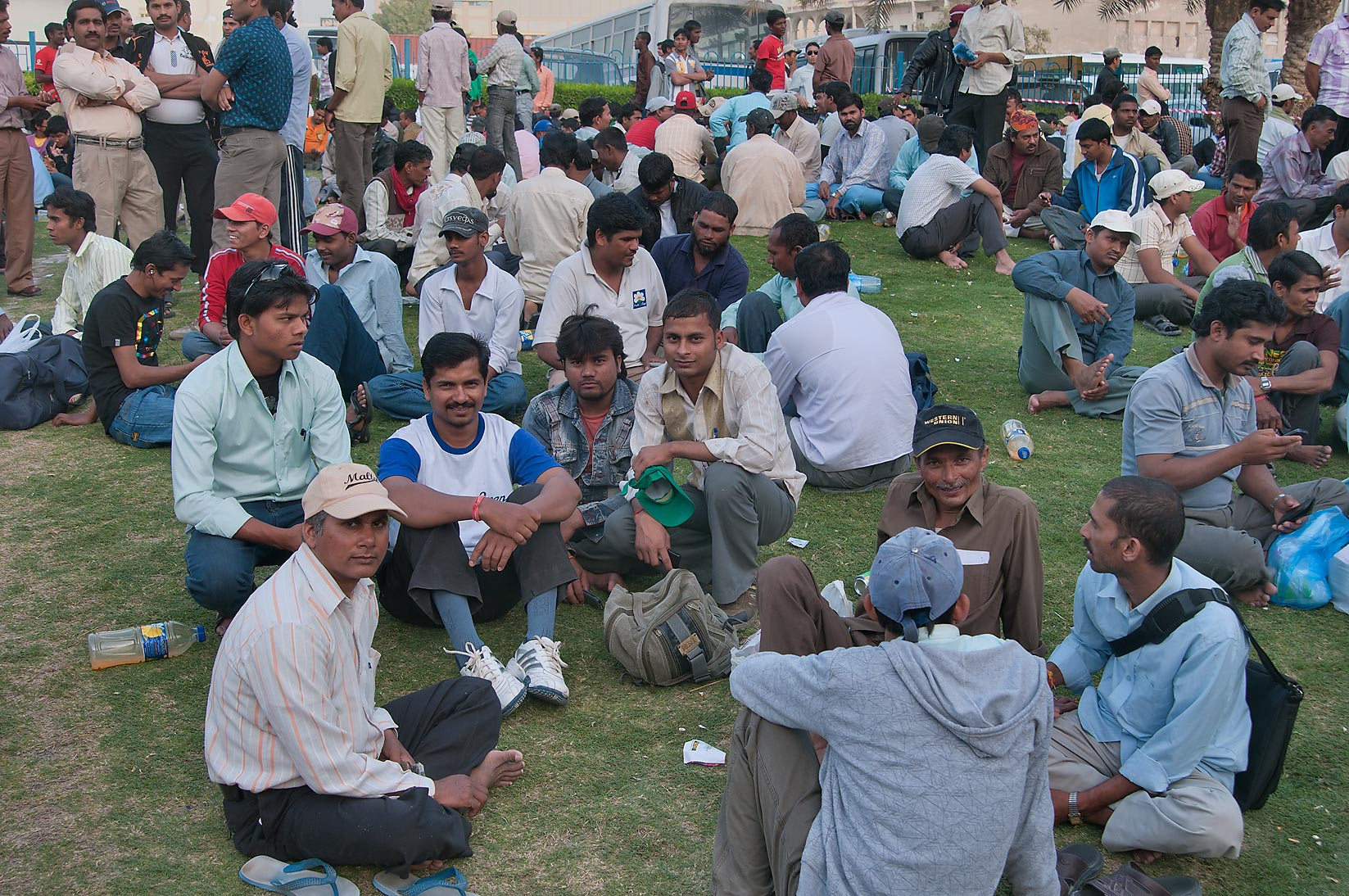 Crowds of migrant workers socializing on Friday...Al Ghanim) Bus Station. Doha, Qatar