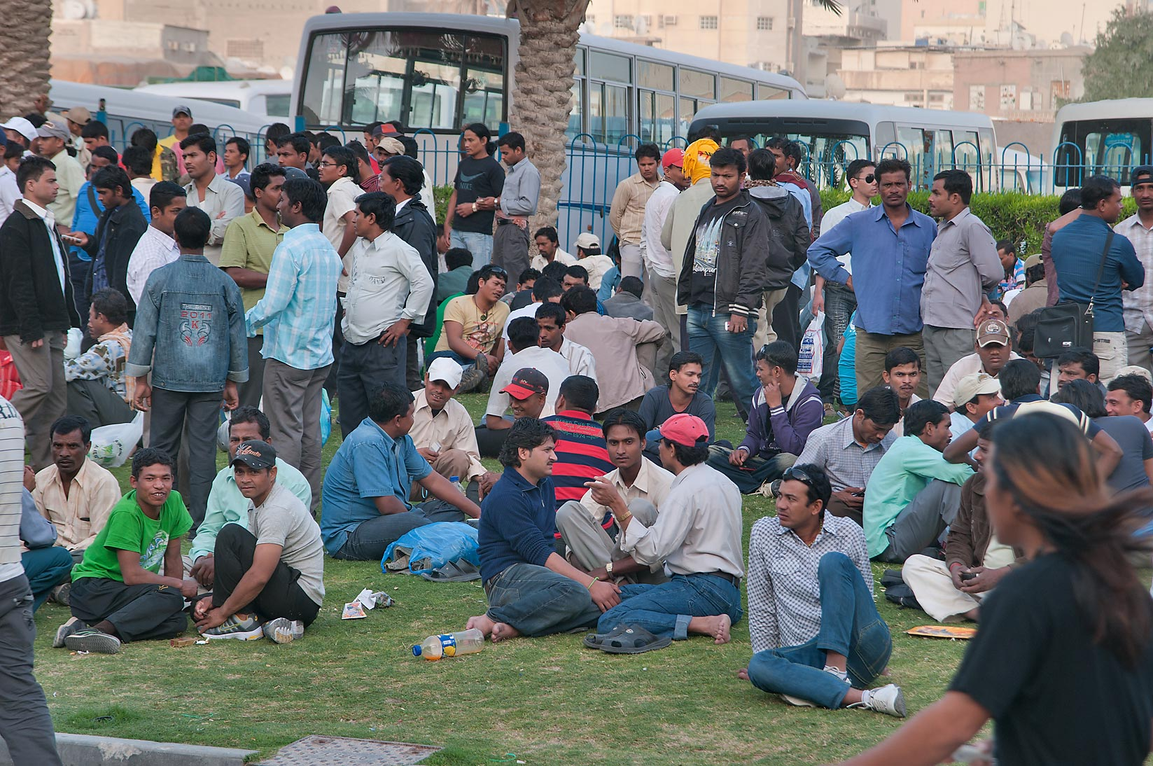 Crowds socializing on Friday evening on a lawn...Al Ghanim) Bus Station. Doha, Qatar