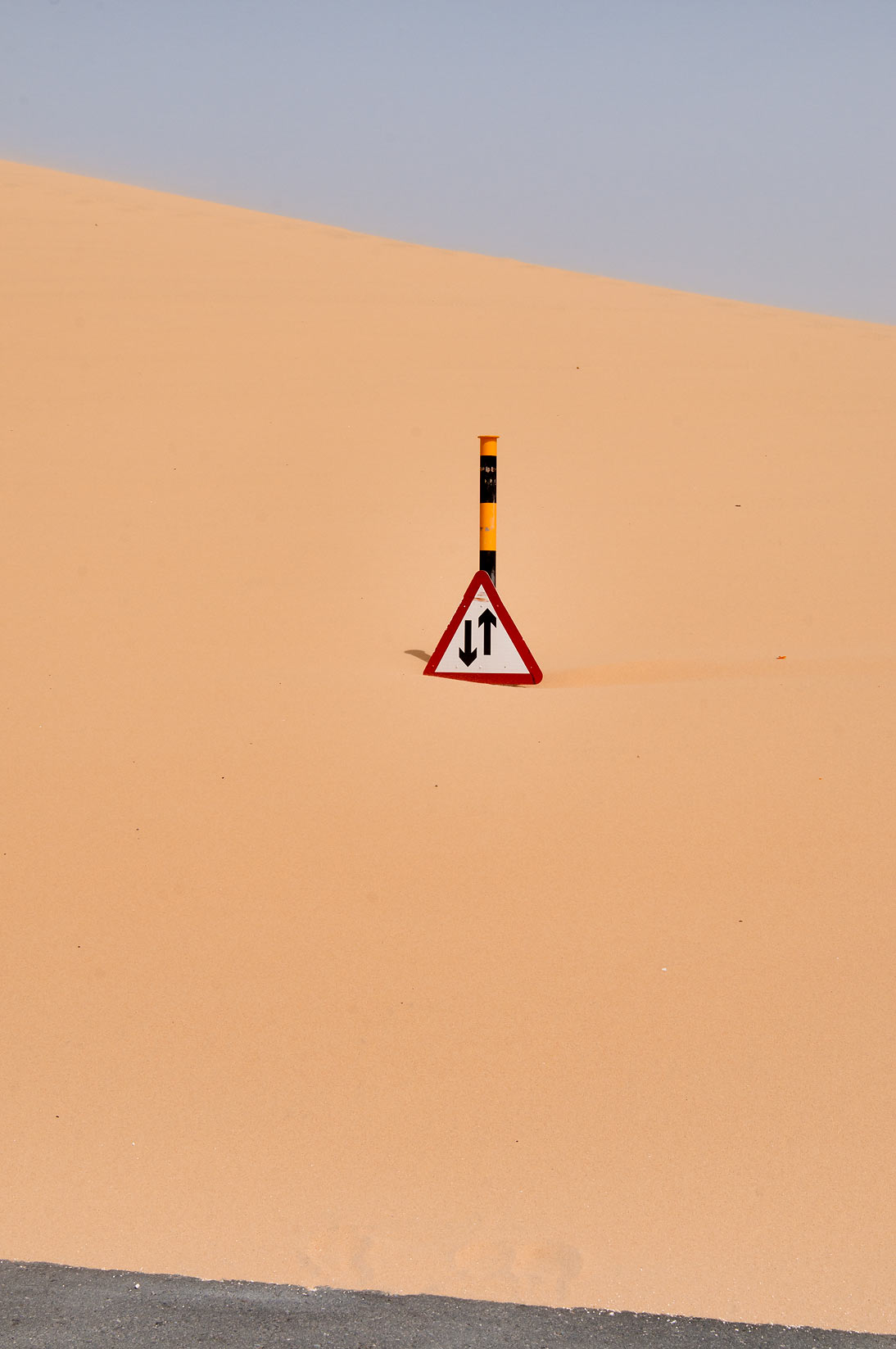 Road sign covered by sand near Singing Sand Dunes near Mesaieed. Qatar