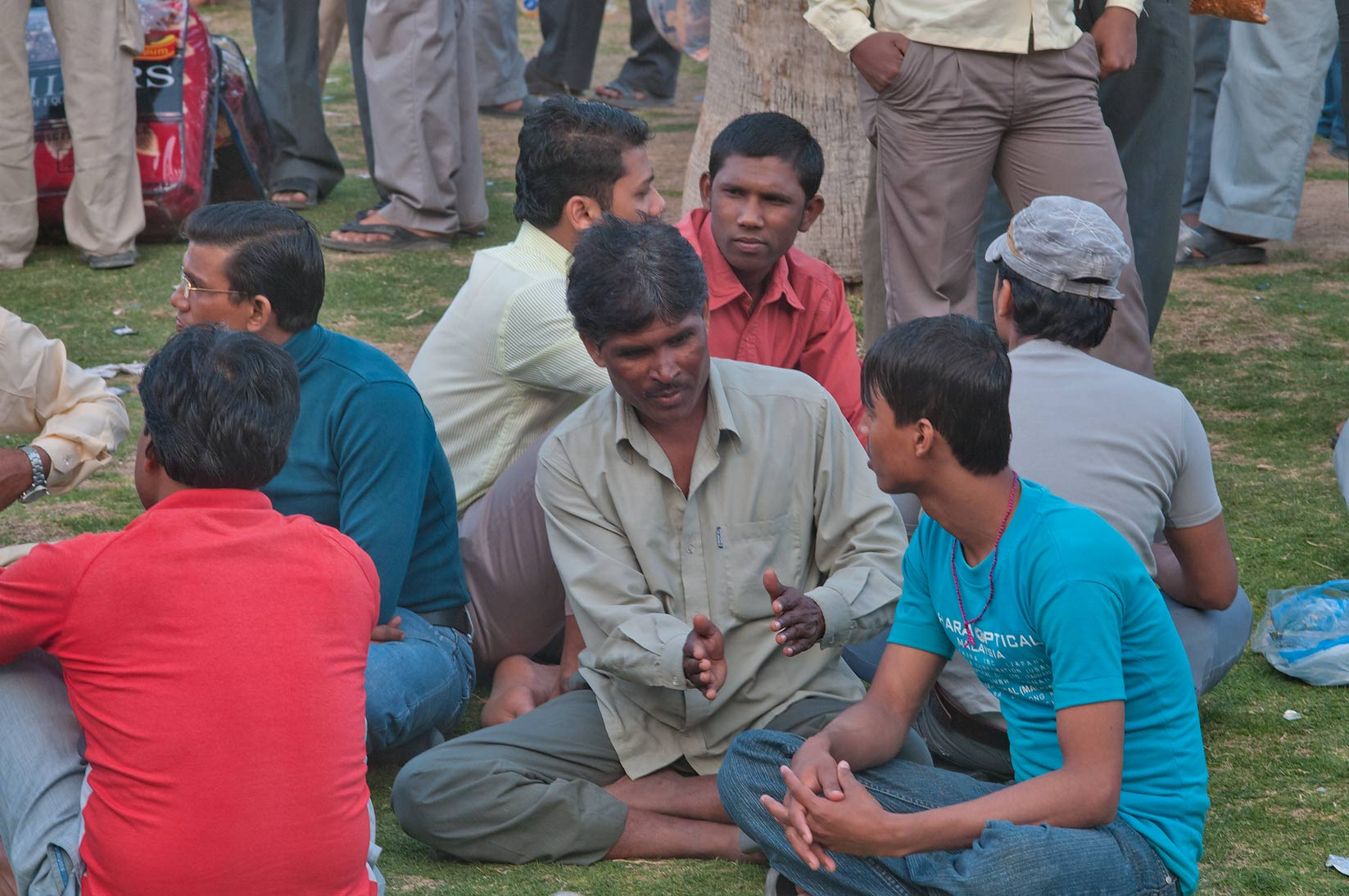 Migrant workers socializing on a lawn near...Al Ghanim on Friday. Doha, Qatar