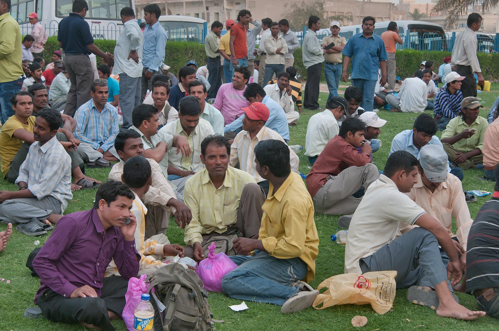 Migrant workers resting on a lawn at Central Bus Station Al Ghanim on Friday. Doha, Qatar