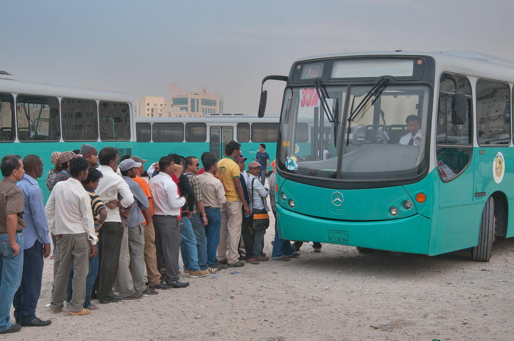 Workers lining to board city bus Karwa at Central Bus Station Al Ghanim. Doha, Qatar