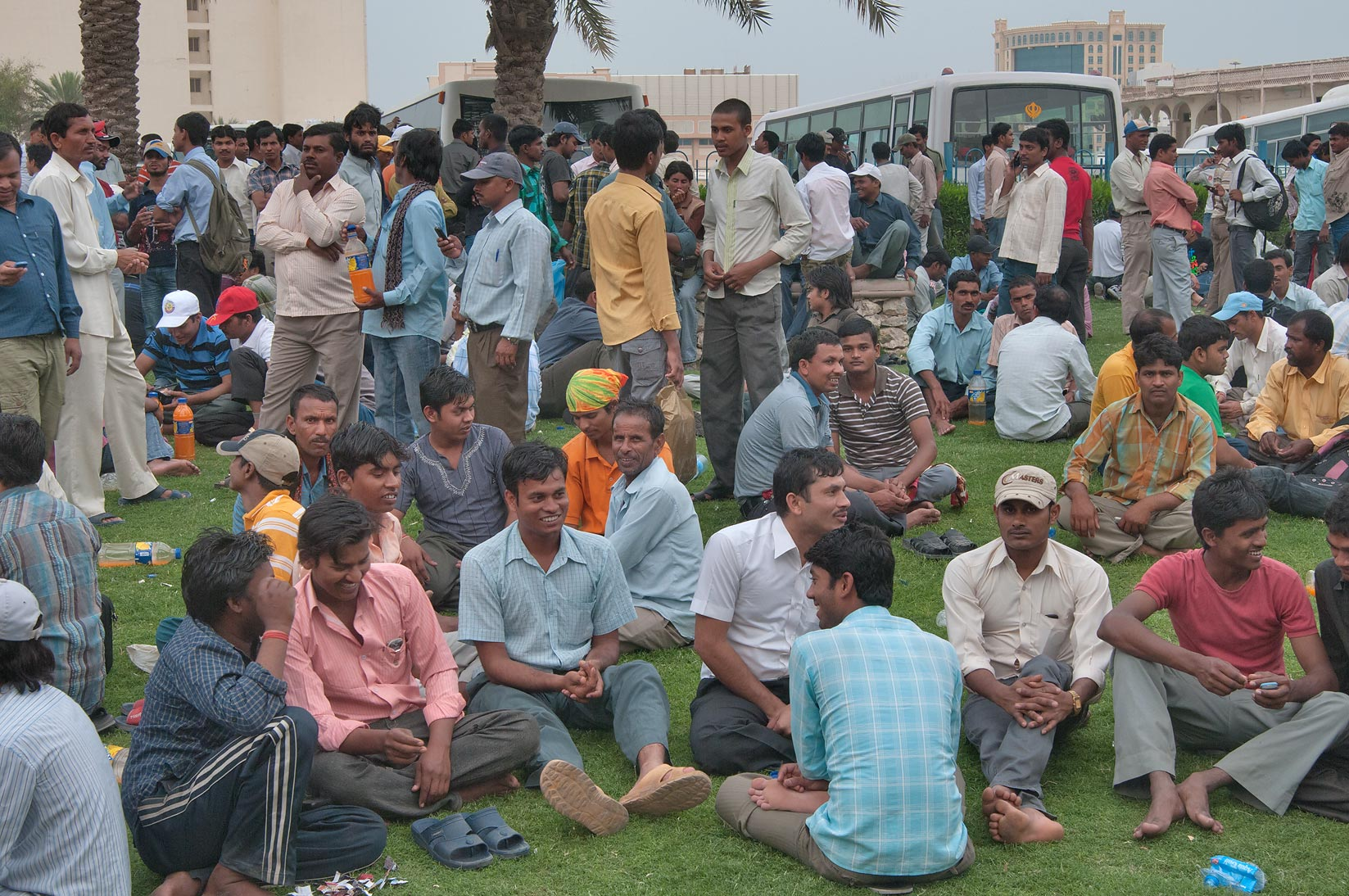 Workers sitting and standing on a lawn on Friday...Bus Station Al Ghanim. Doha, Qatar