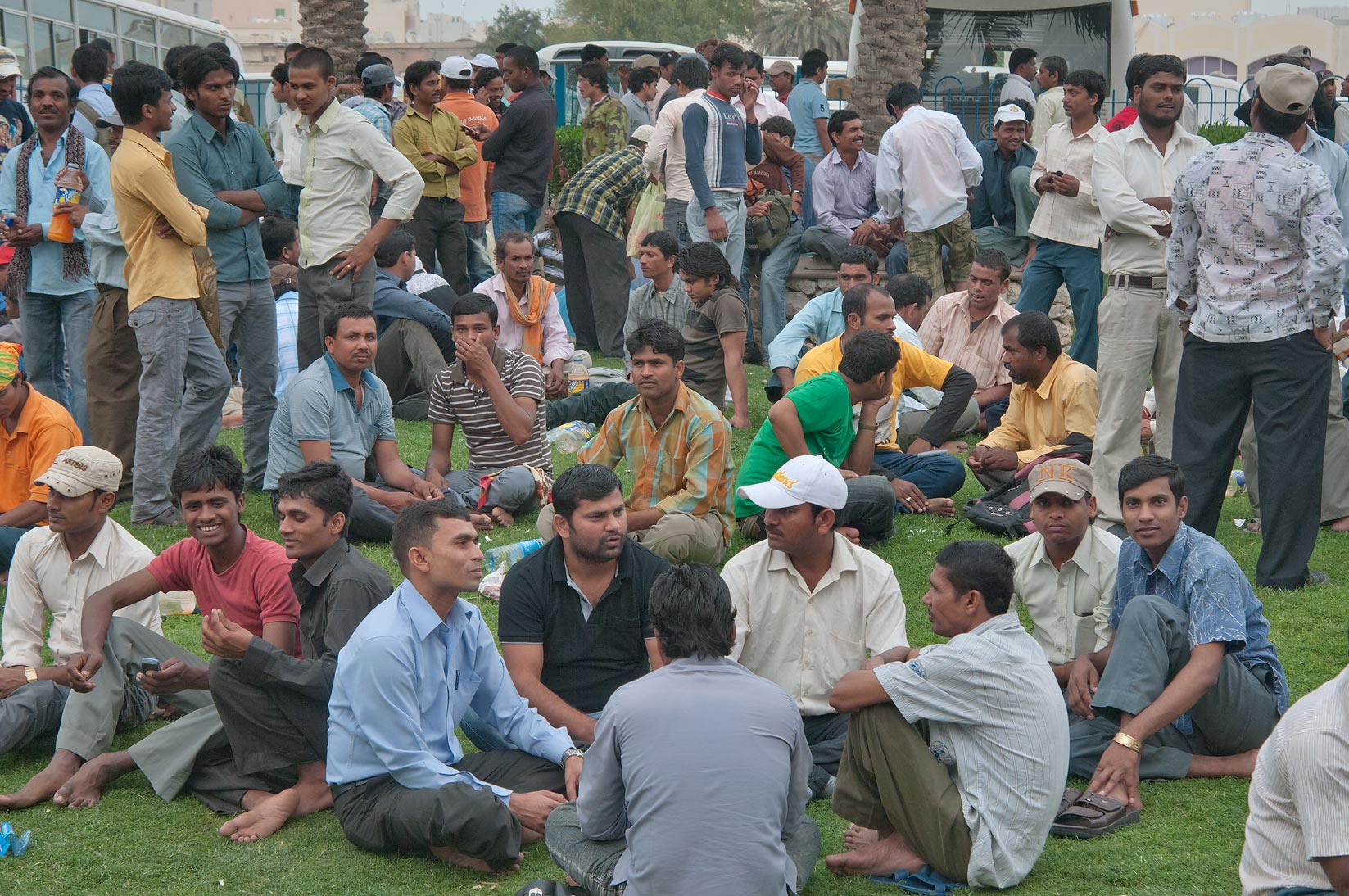 Migrant workers socializing on a lawn on Friday...Bus Station Al Ghanim. Doha, Qatar