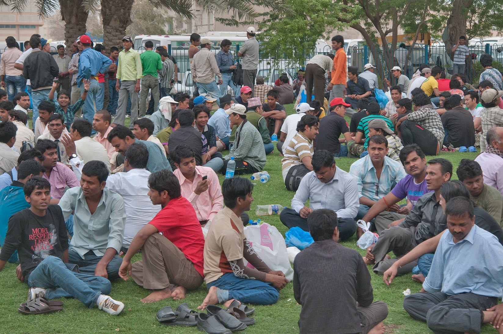 Migrant workers resting on a lawn on Friday...Bus Station Al Ghanim. Doha, Qatar