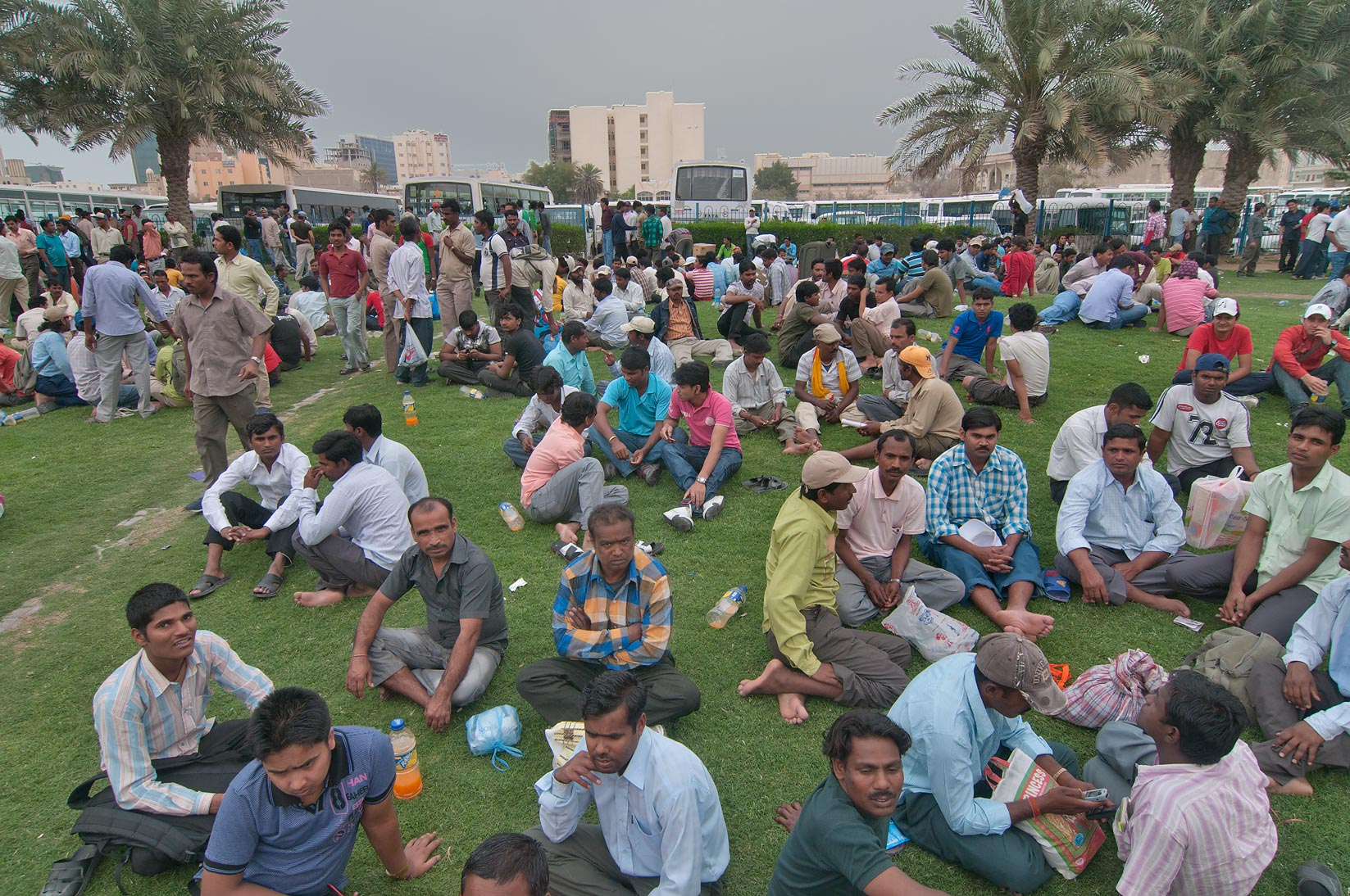 Crowds of migrant workers on a lawn on Friday...Bus Station Al Ghanim. Doha, Qatar