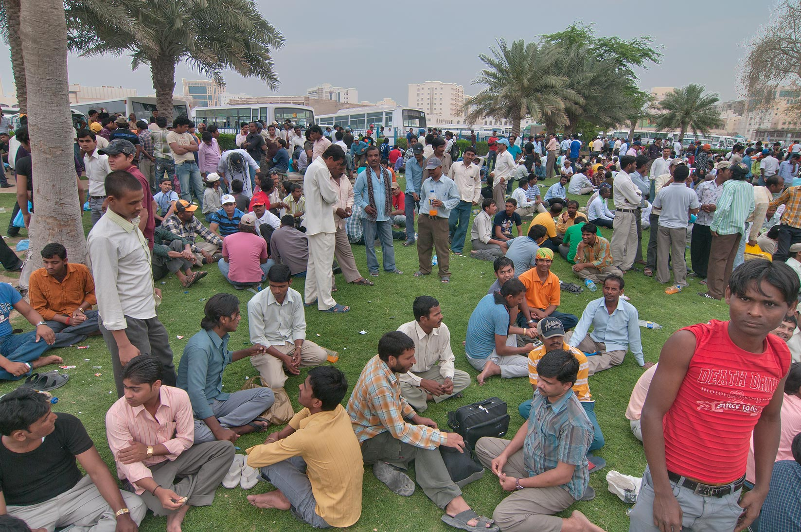 Crowds of migrant workers resting on a lawn on...Bus Station Al Ghanim. Doha, Qatar