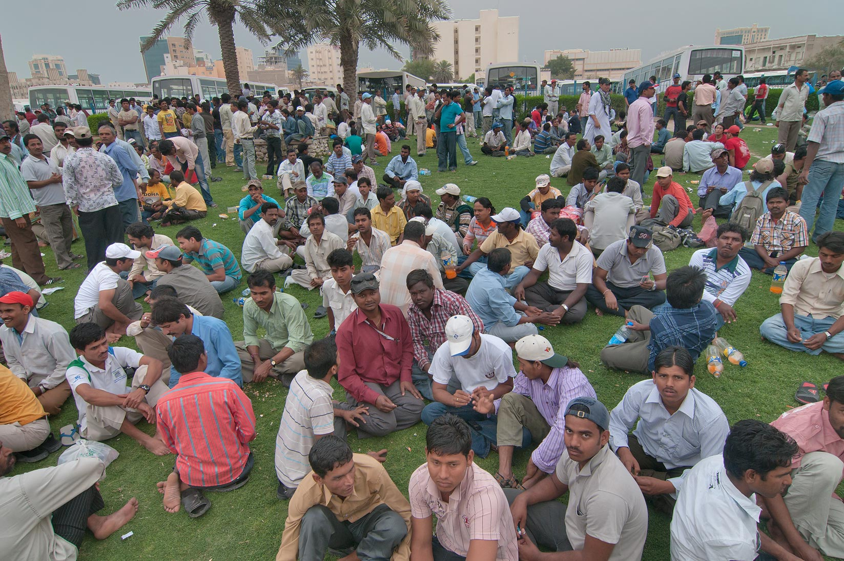 Weekend crowds of migrant workers resting on a...Bus Station Al Ghanim. Doha, Qatar