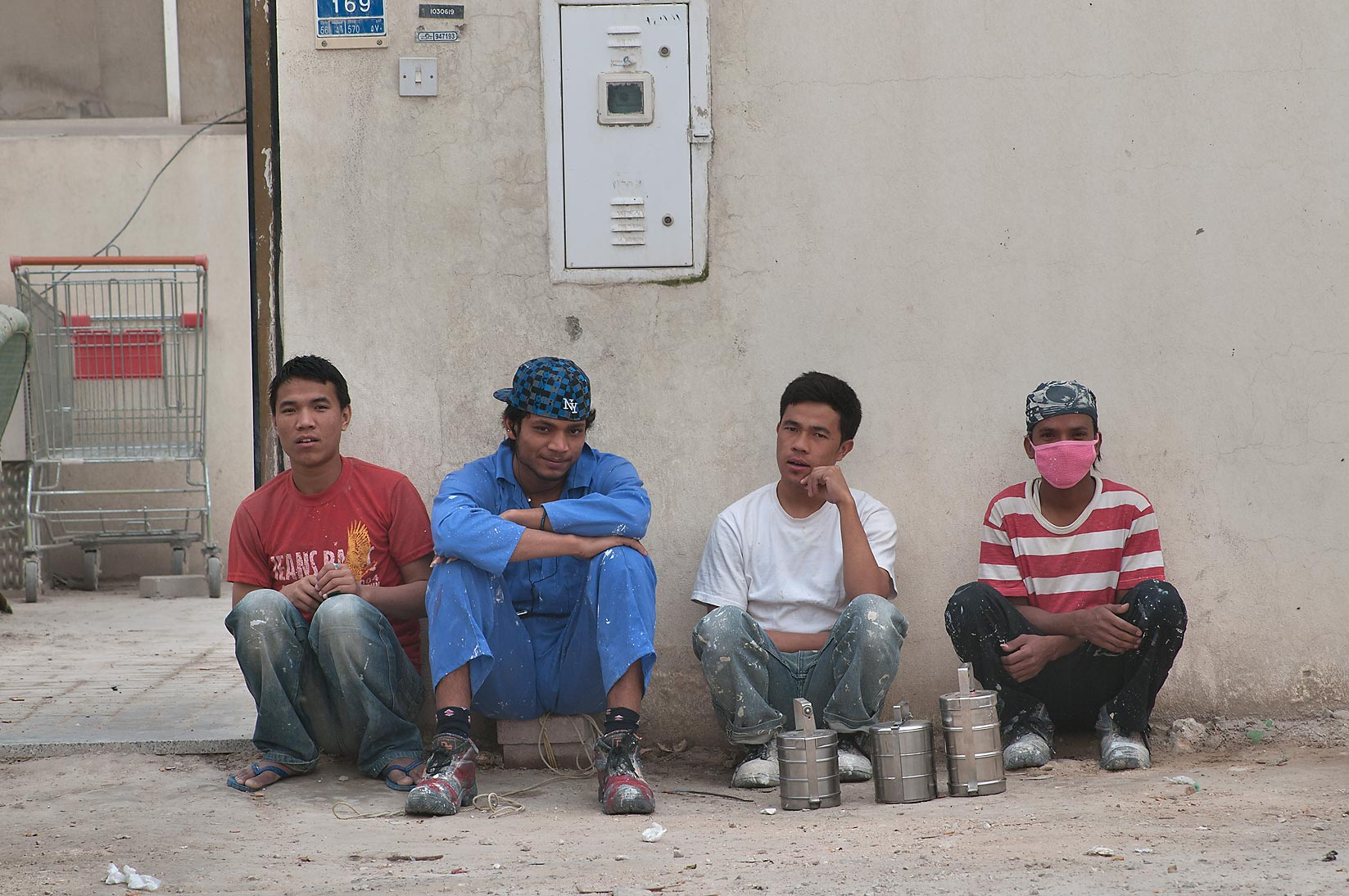 Workers sitting during dust storm near Camel Market, Wholesale Markets area. Doha, Qatar