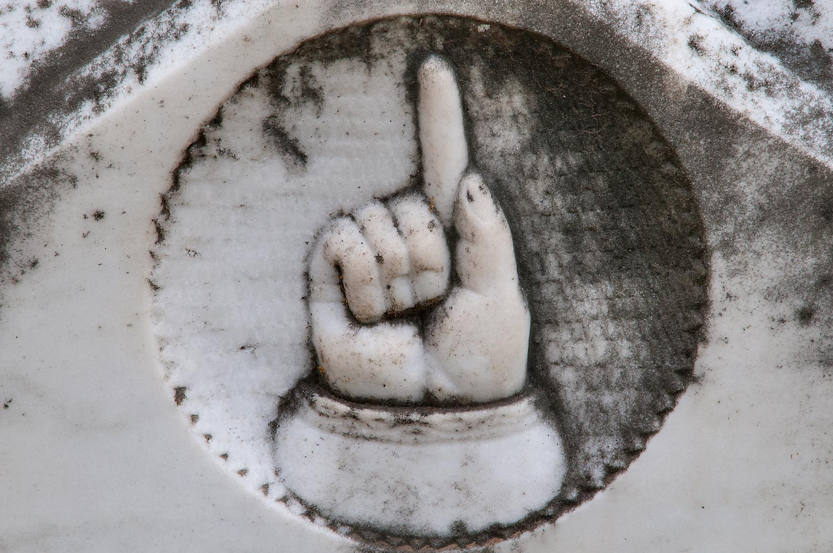 Hand with index finger pointing upward in City Cemetery. Bryan, Texas