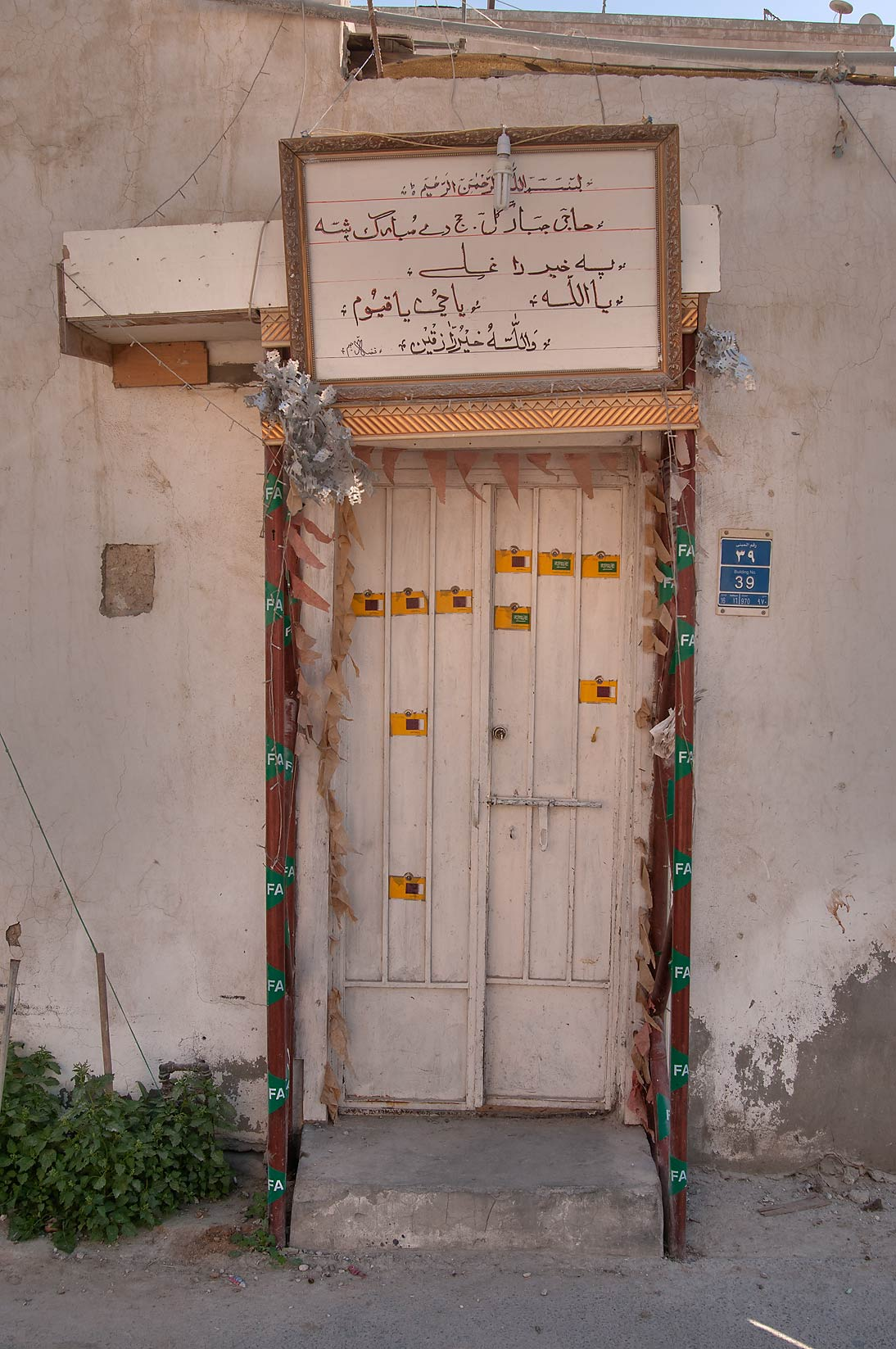A door decorated by stickers with flags near Tariq Bin Ziyad St.. Doha, Qatar