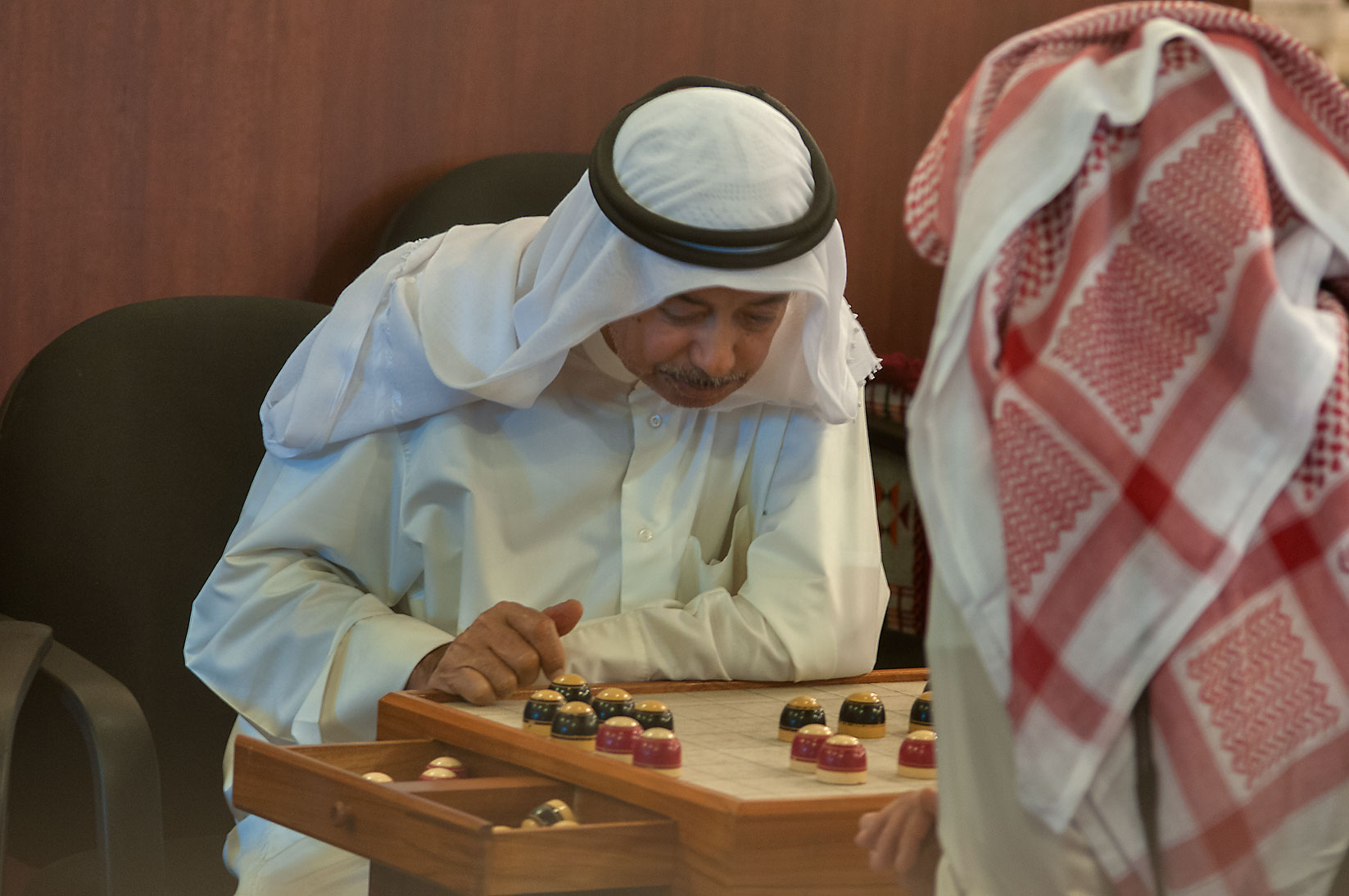 Playing traditional board game of Damah in Souq Waqif (Old Market). Doha, Qatar