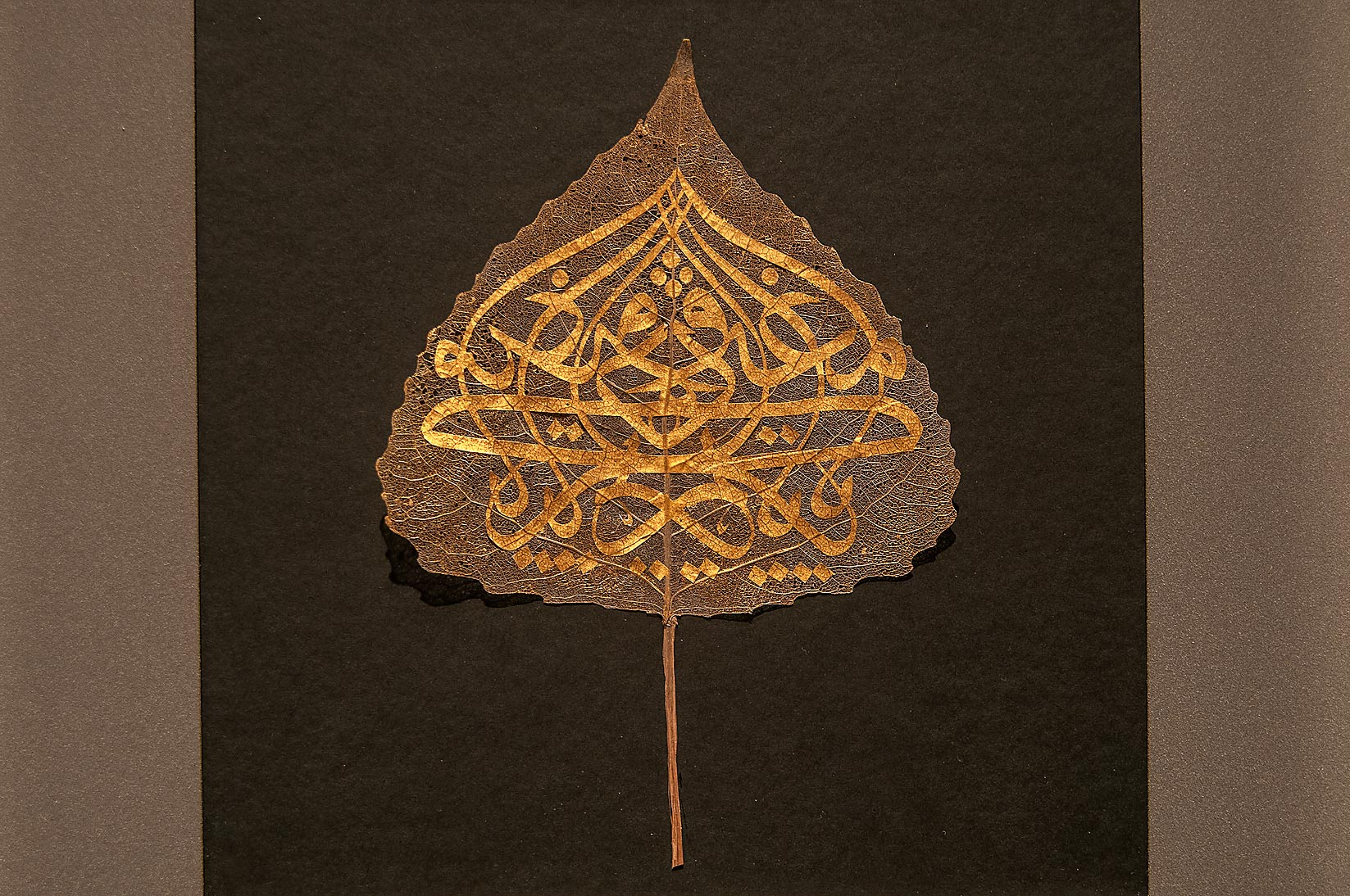 Arabic calligraphy on a natural leaf (gold) in Museum of Islamic Art. Doha, Qatar