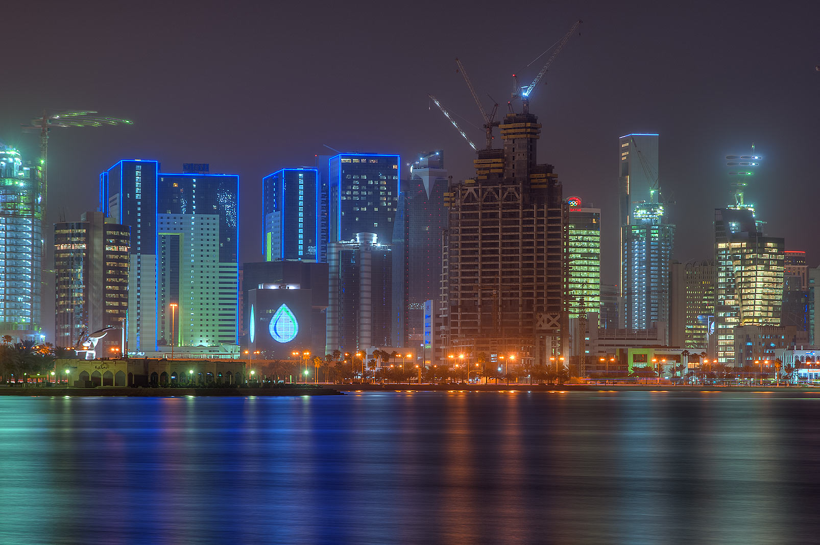 Glowing towers of West Bay area from Corniche promenade. Doha, Qatar