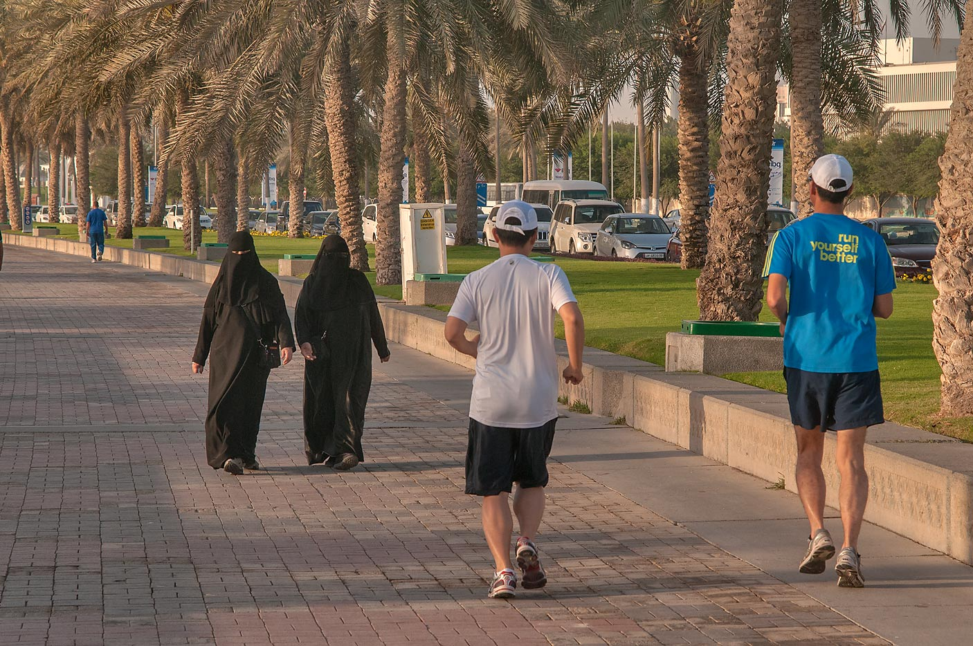 People in various dress jogging on Corniche promenade at morning. Doha, Qatar